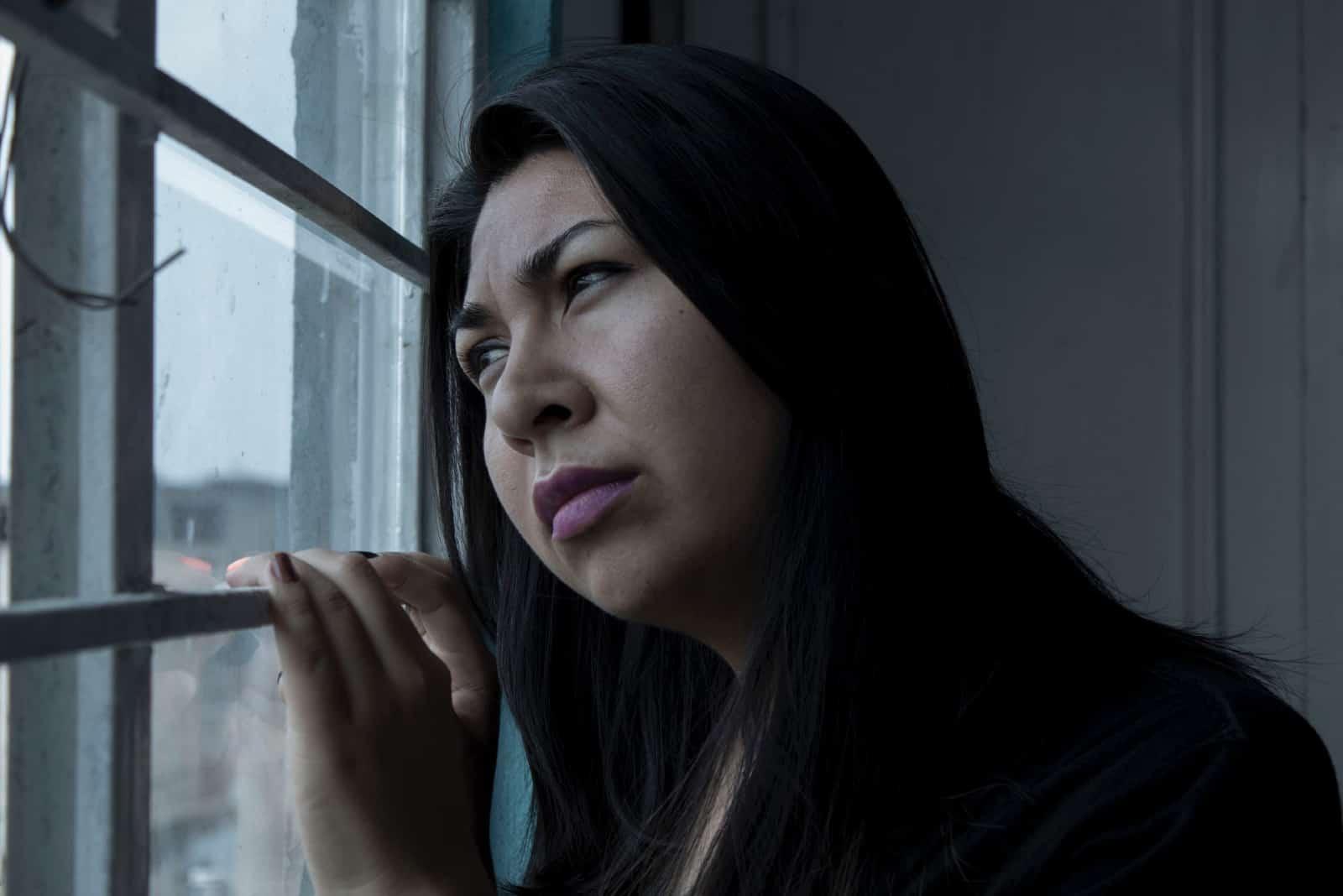 femme pensive avec du rouge à lèvres rose regardant par la fenêtre