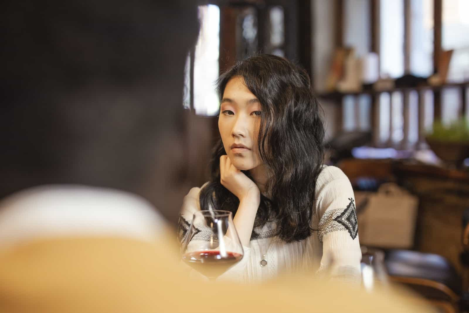 Une femme sérieuse regarde un homme assis dans un café