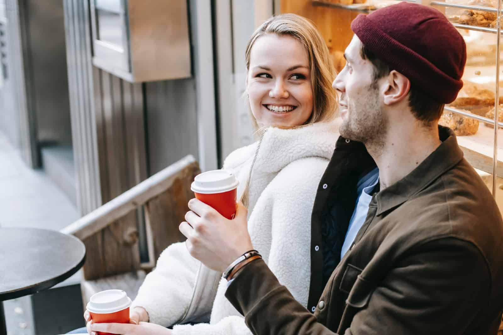 femme heureuse regardant un homme assis à l'extérieur