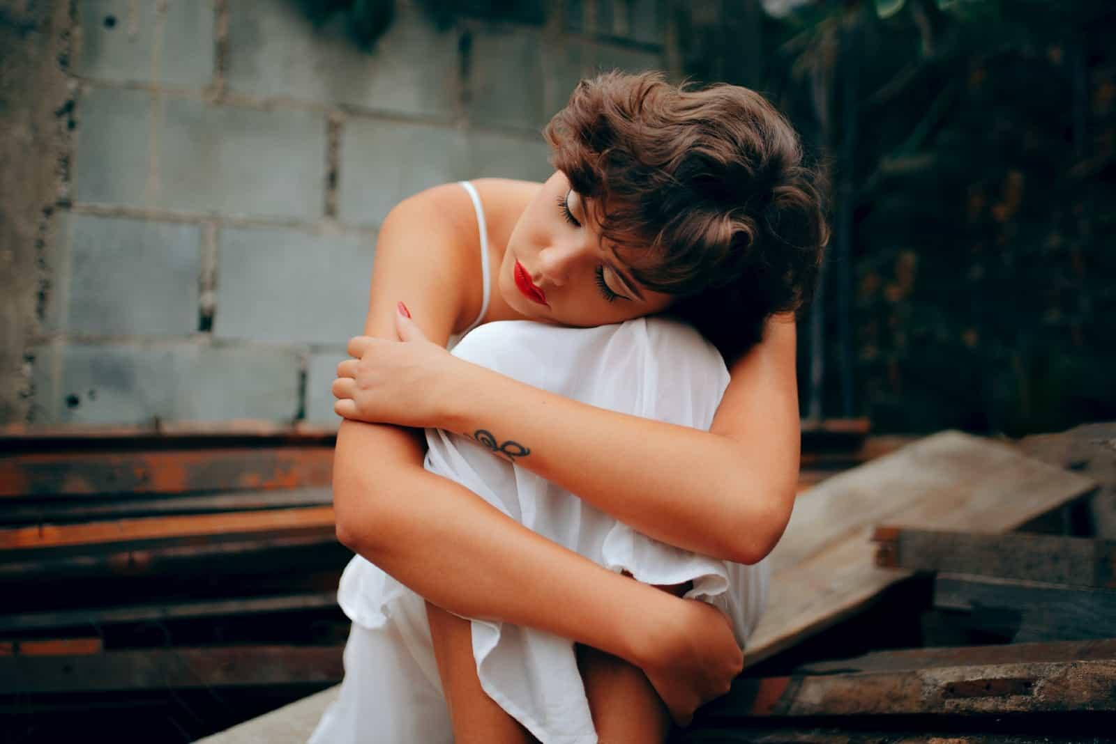 femme triste en robe blanche serrant ses genoux