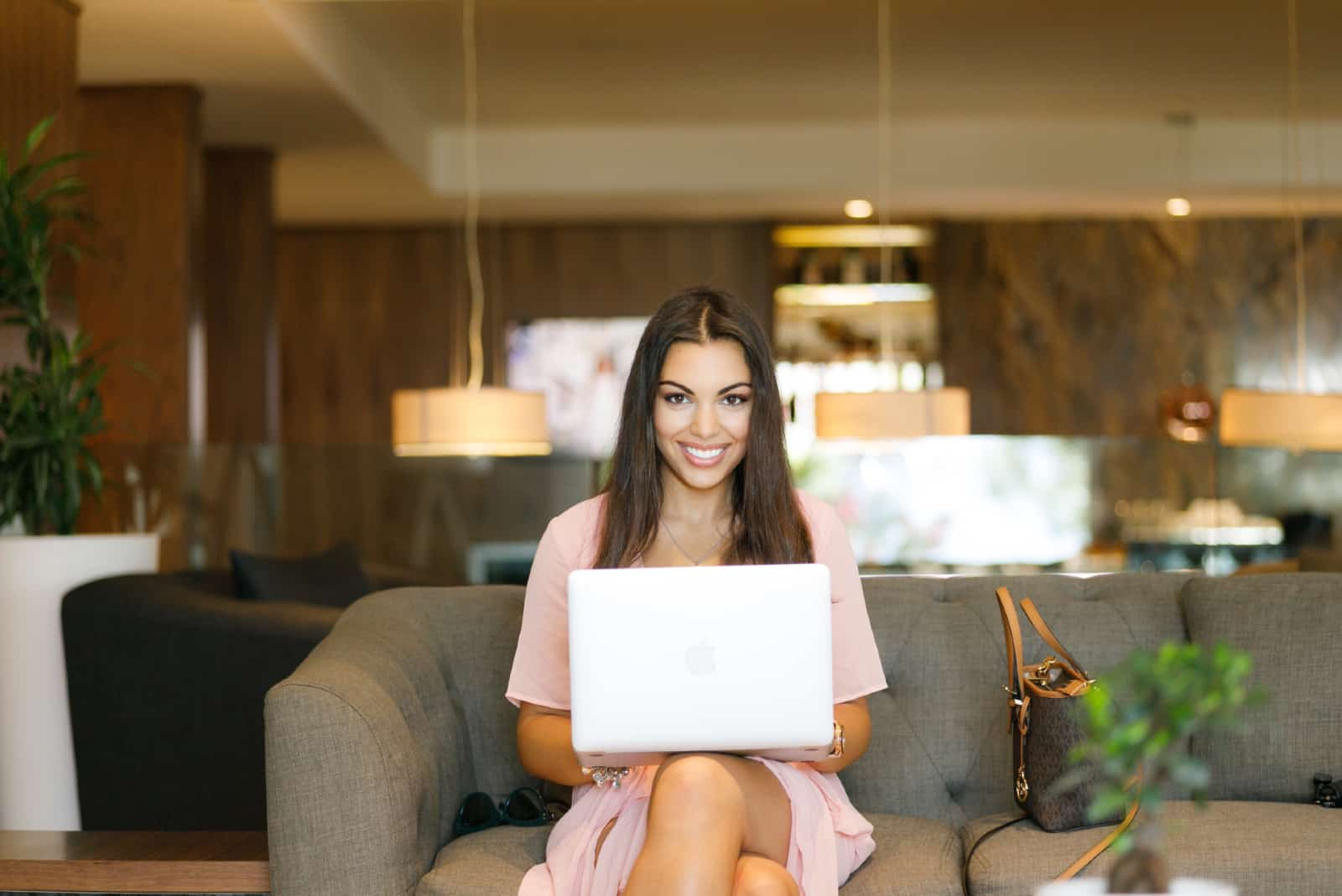 femme heureuse en robe rose tenant un ordinateur portable