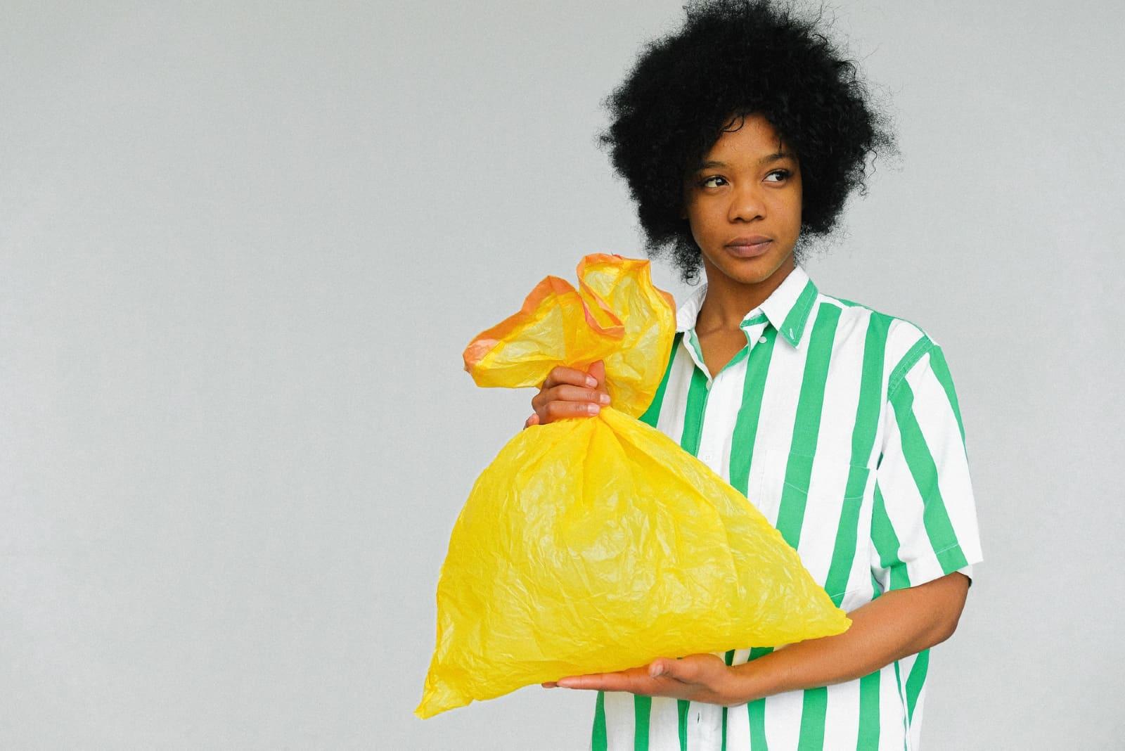 femme aux cheveux bouclés tenant un sac en plastique jaune