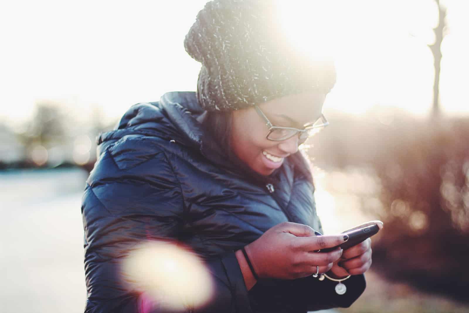 femme heureuse avec un bonnet en tricot utilisant un smartphone