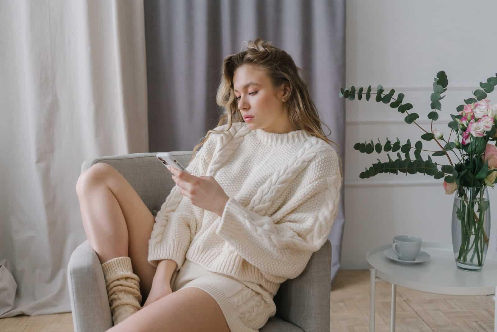 Une femme utilise un smartphone alors qu'elle est assise sur un fauteuil gris