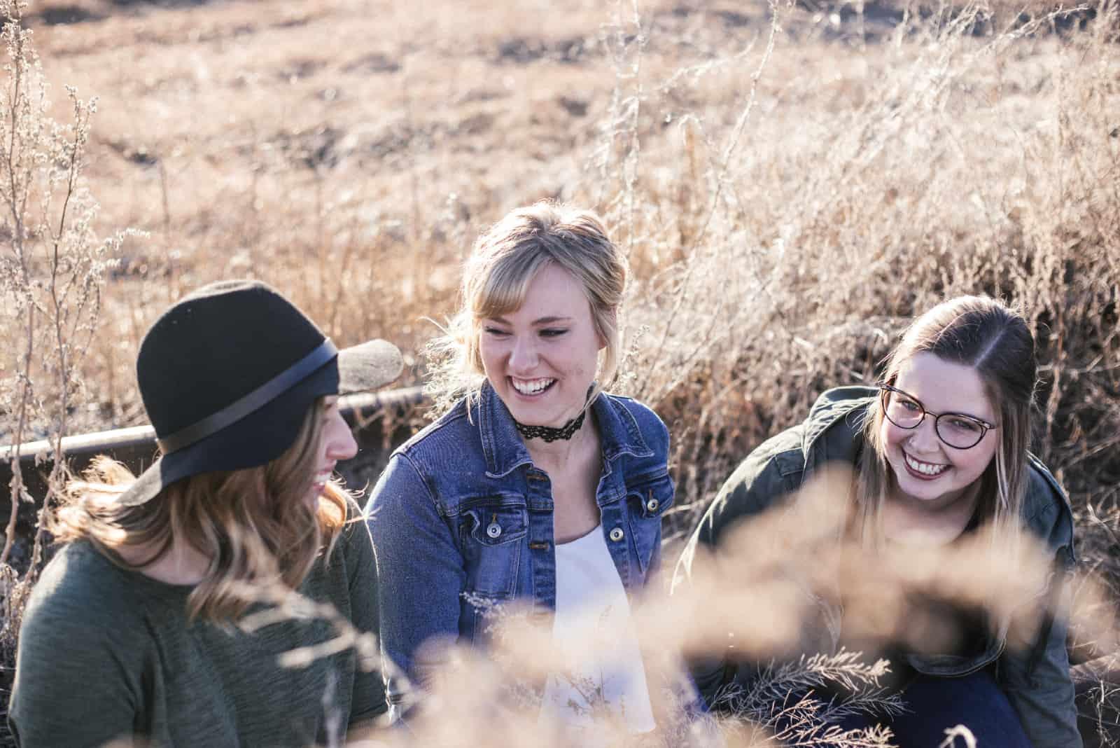 trois femmes souriant en plein air