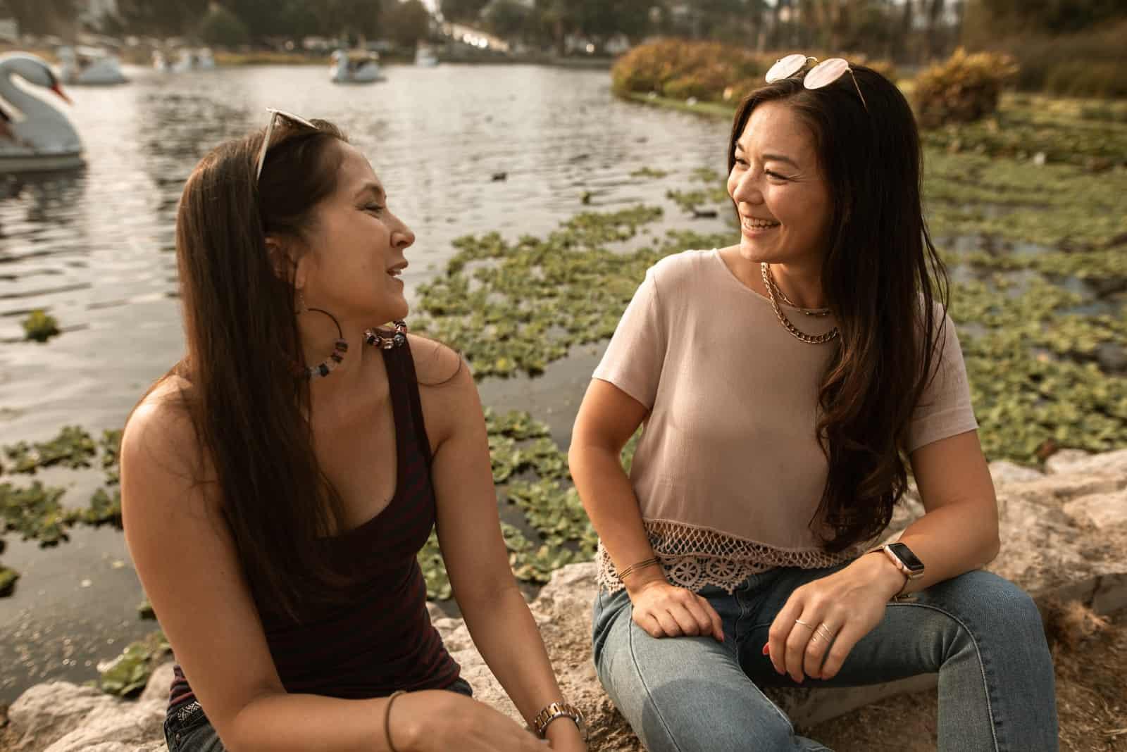 deux femmes discutant assises près de l'eau