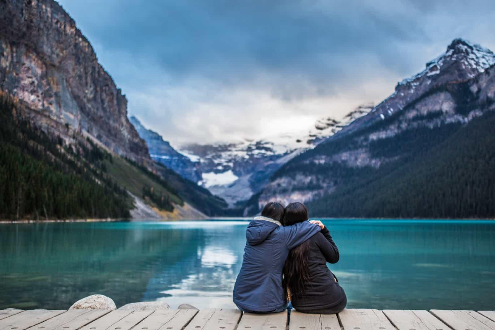 deux femmes s'étreignent en s'asseyant sur un quai