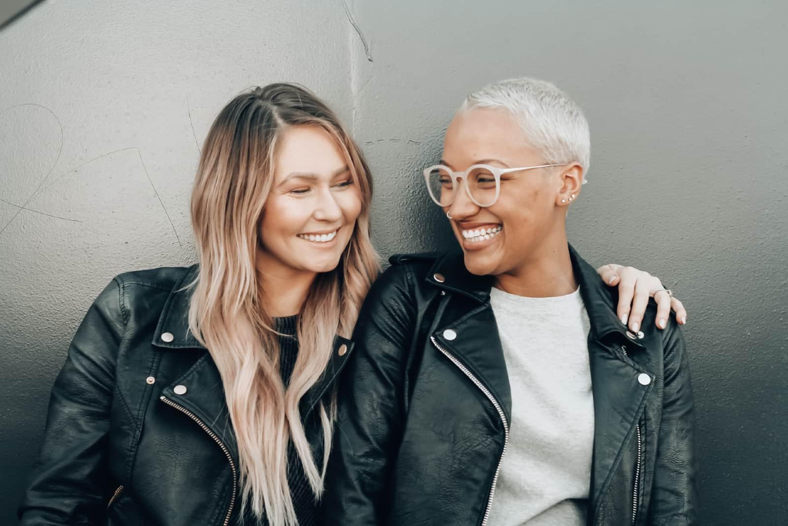 deux femmes heureuses debout près d'un mur