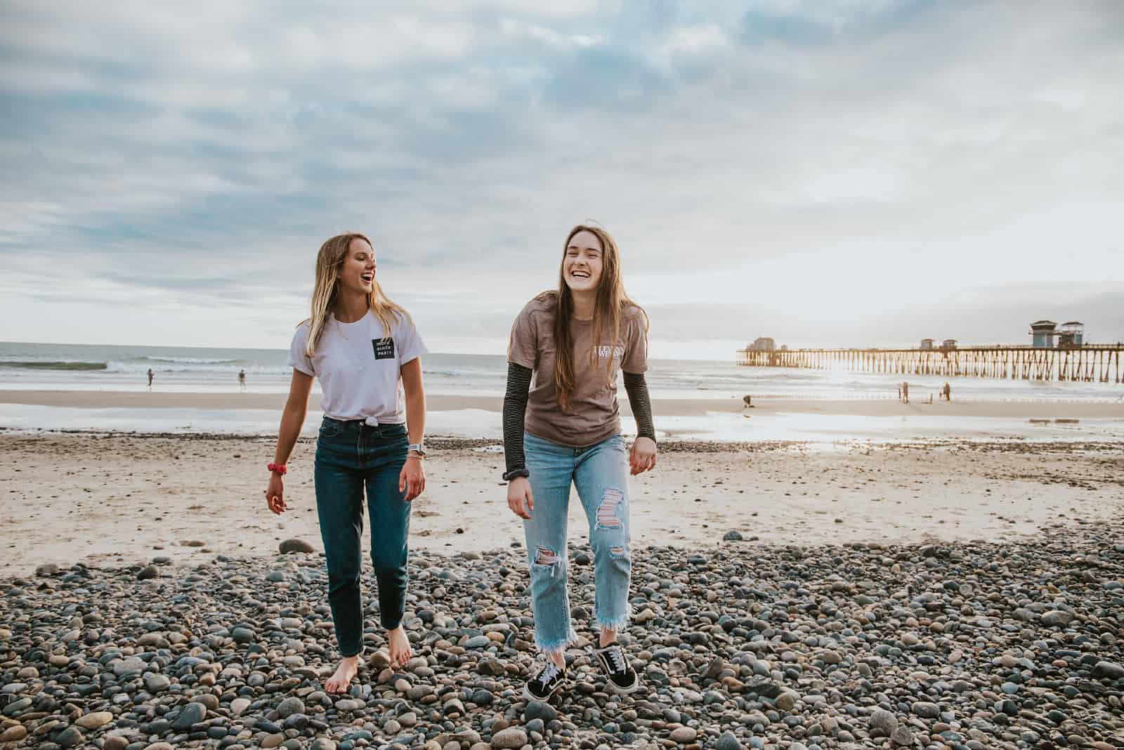 deux femmes riant en marchant sur des cailloux