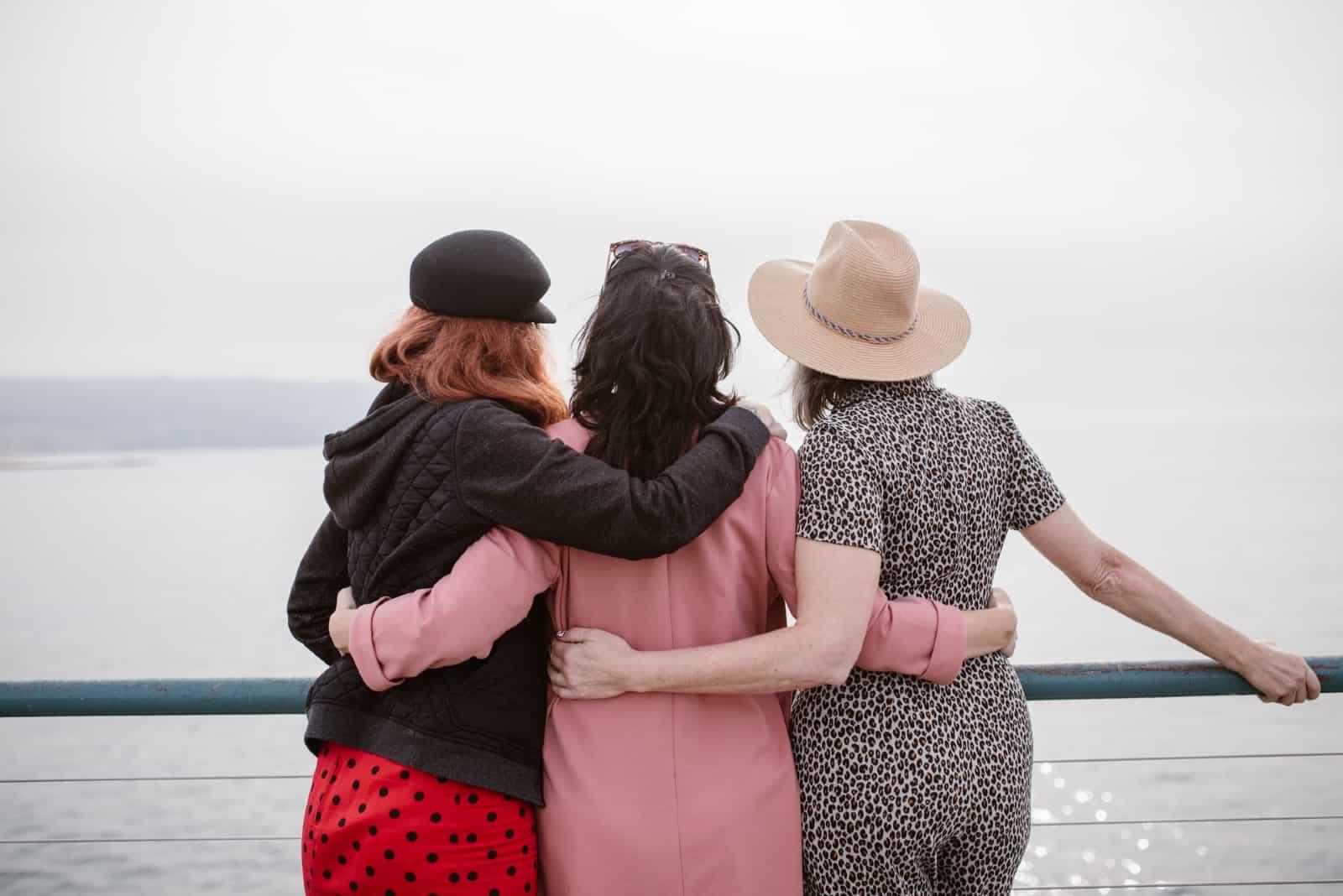 quatre femmes âgées s'embrassant en regardant l'eau