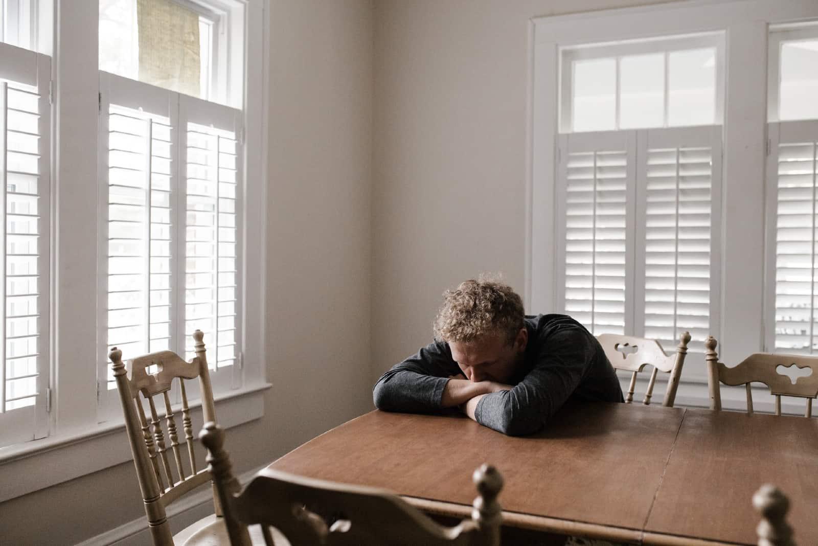 homme triste appuyé sur une table près d'une fenêtre