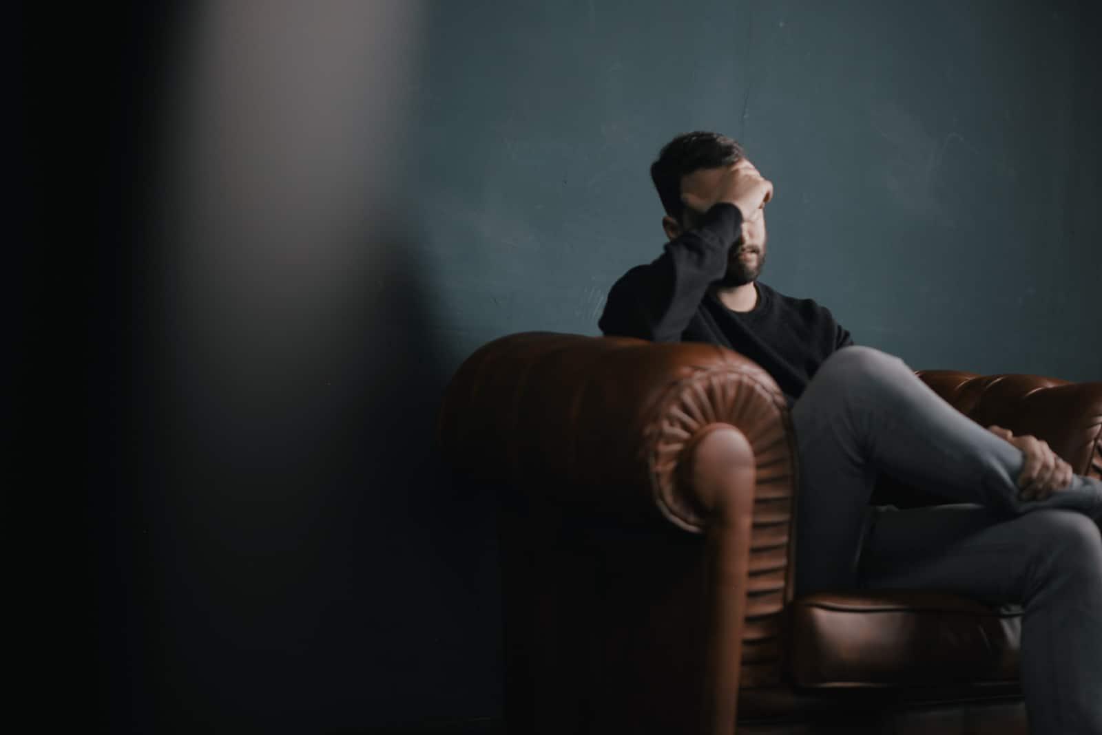 homme triste en sweat-shirt noir assis sur un canapé