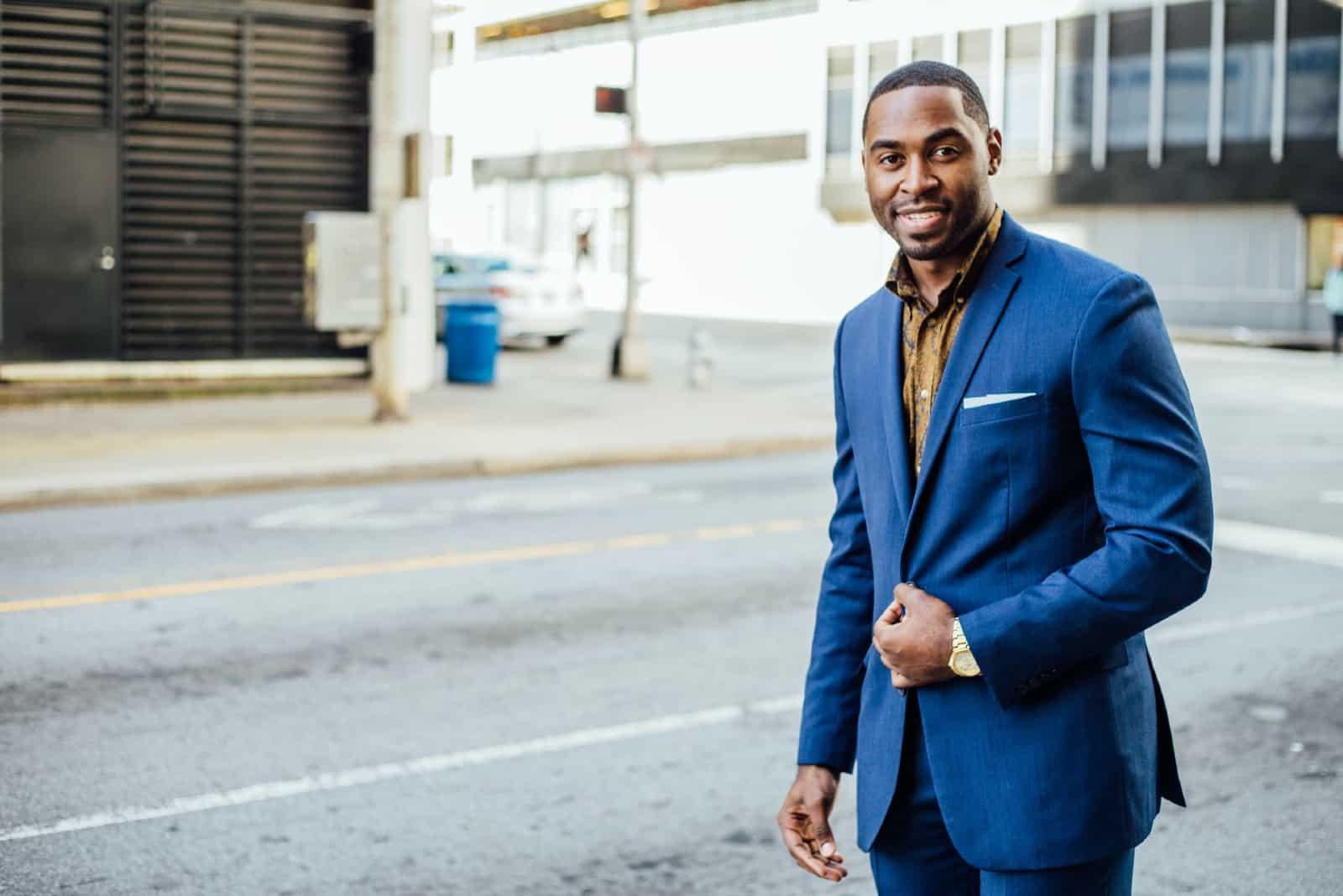 homme heureux en costume bleu debout dans la rue