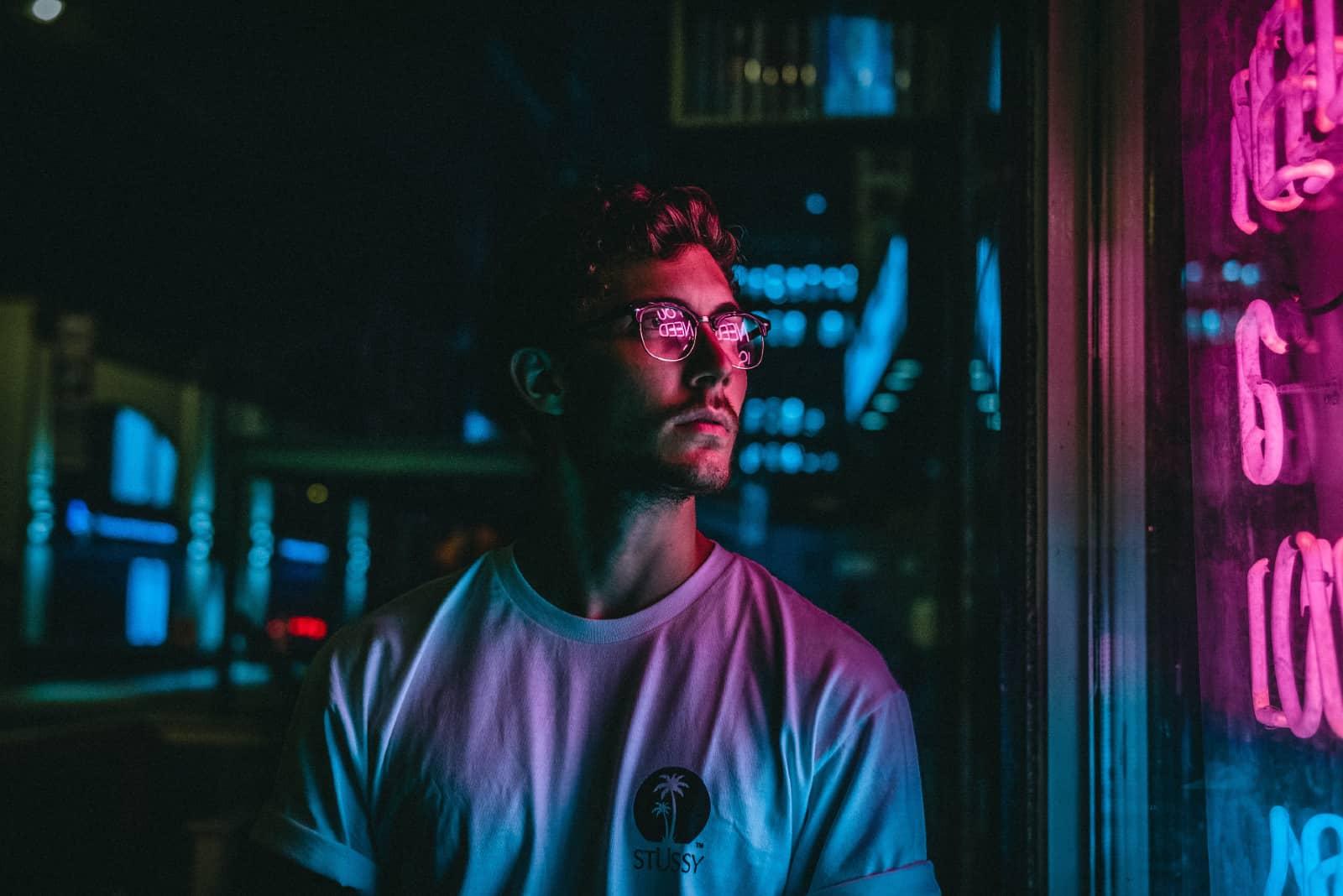 homme avec des lunettes debout à l'extérieur la nuit