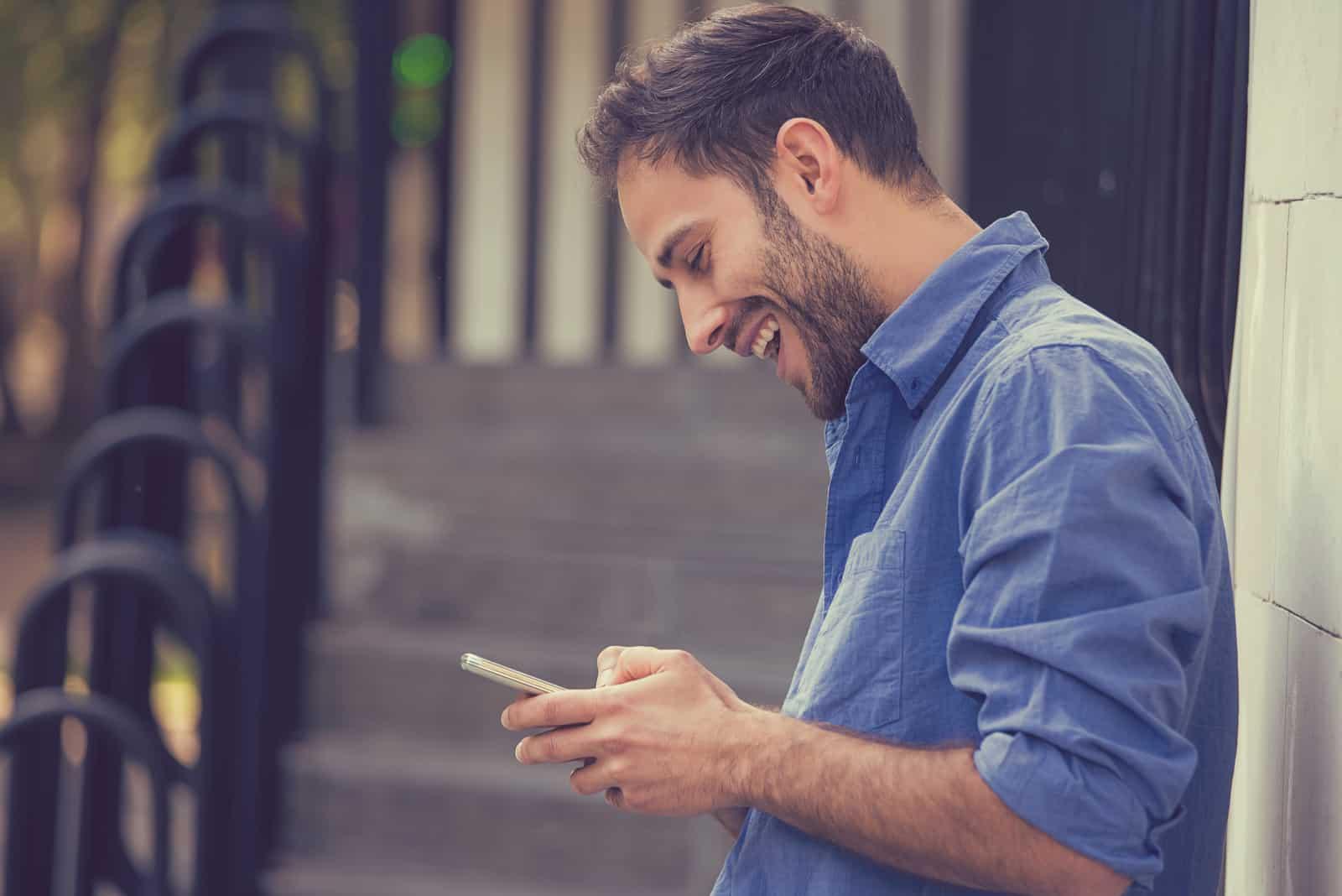 un homme utilise un smartphone tout en se tenant près d'un mur