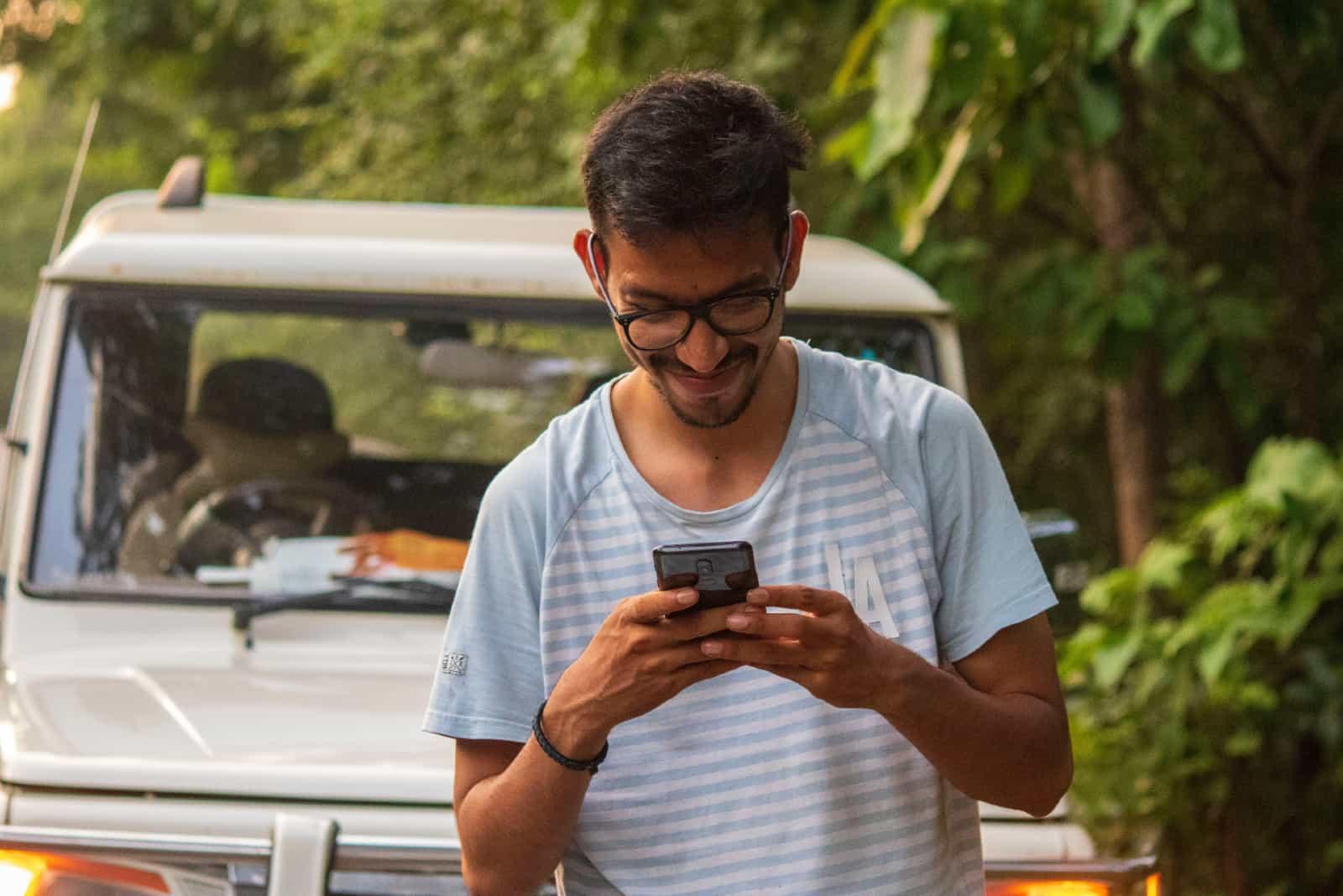 Homme heureux utilisant un smartphone tout en se tenant près d'une voiture