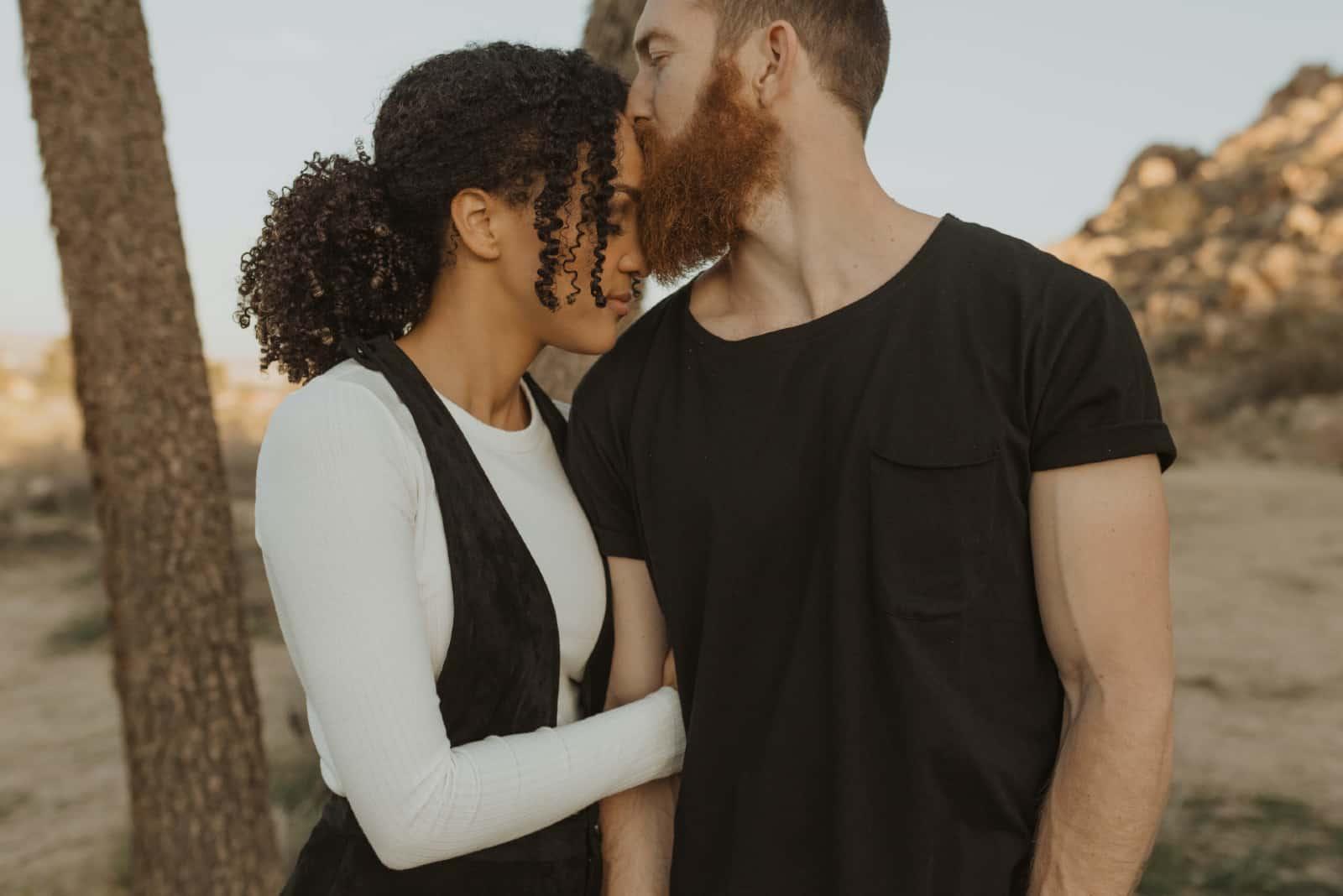 homme embrassant le front d'une femme debout en plein air
