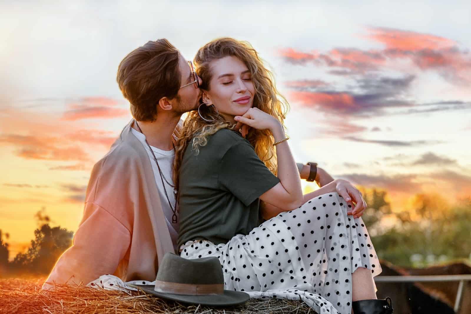 homme embrassant une femme assise en plein air