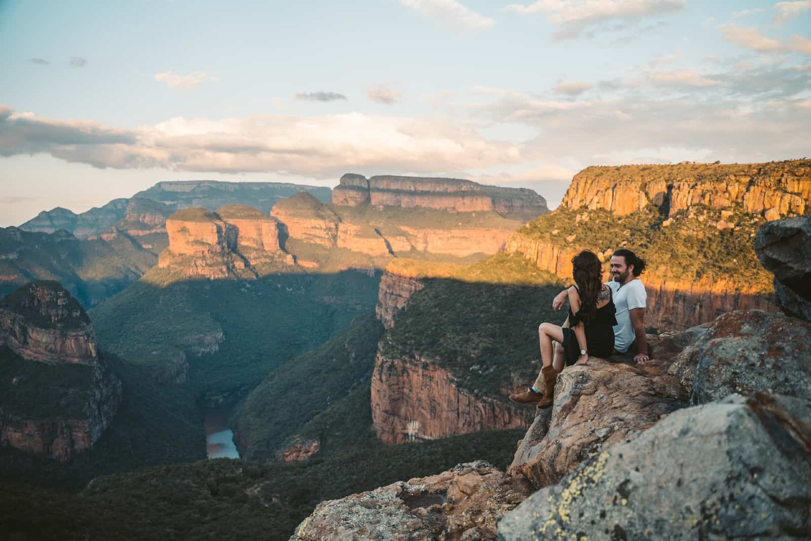 homme heureux regardant une femme assise sur un rocher
