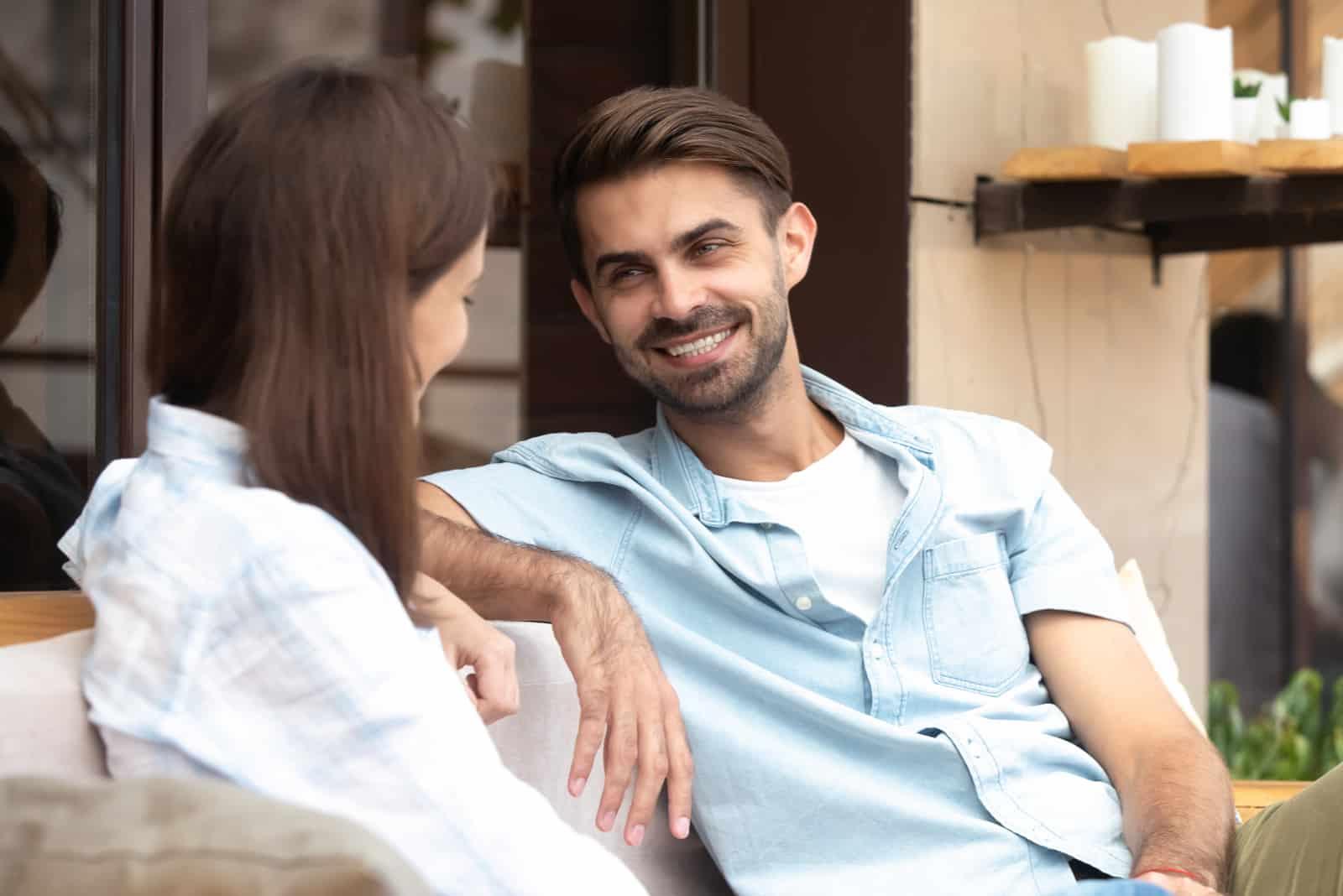 homme heureux regardant une femme assise en plein air