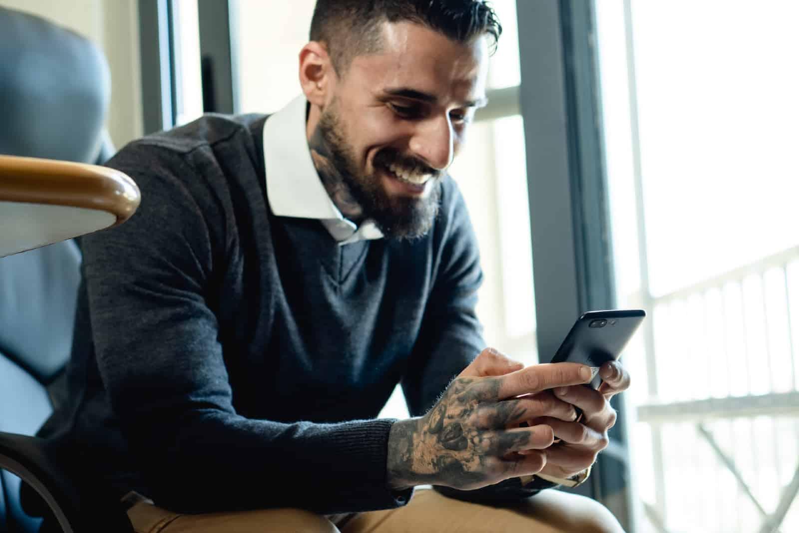 homme barbu heureux utilisant un smartphone