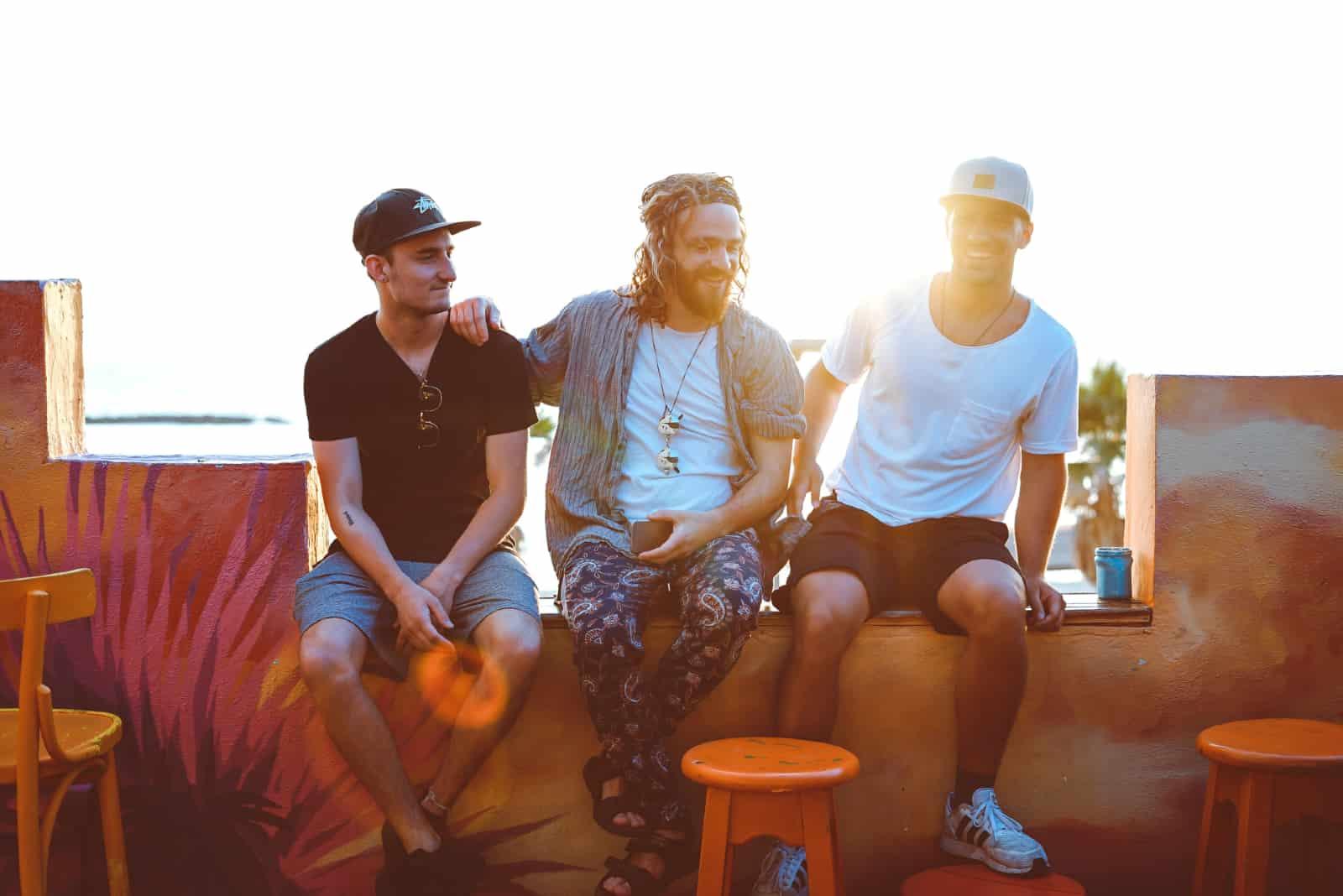trois hommes discutant assis en plein air