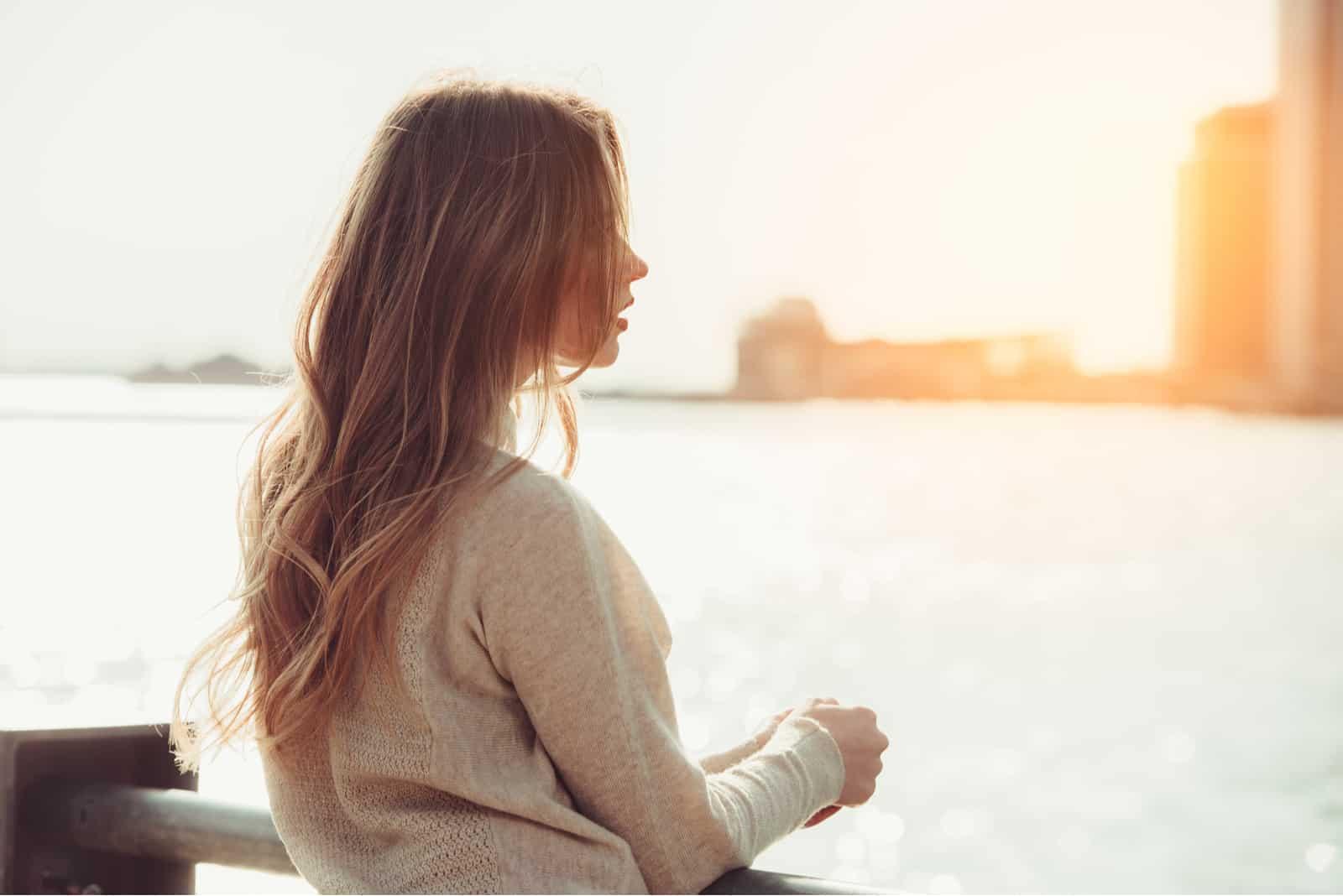 la femme se tient appuyée contre la balustrade et regarde vers la mer
