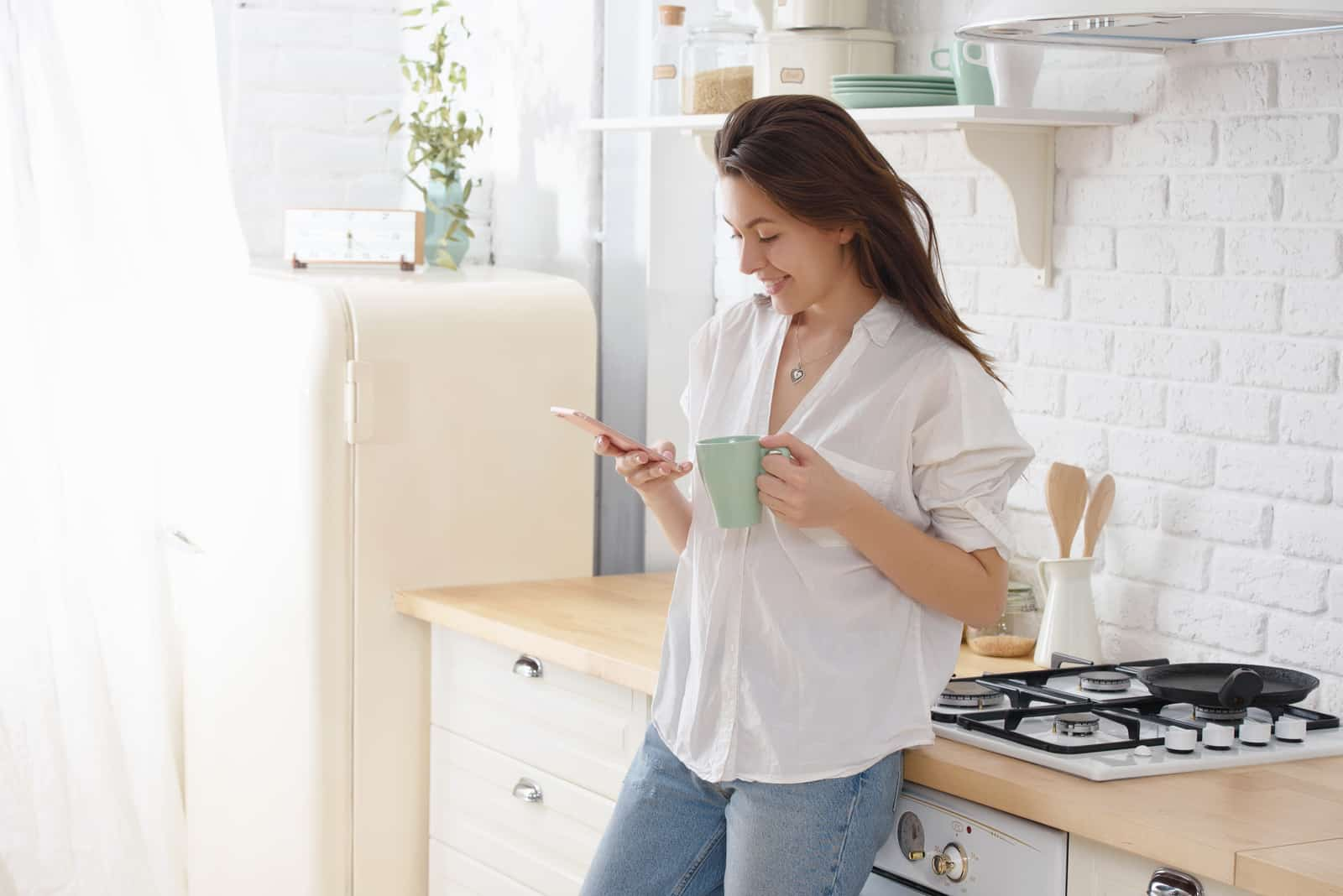 la femme se tient appuyée contre la cuisine et le bouton du téléphone