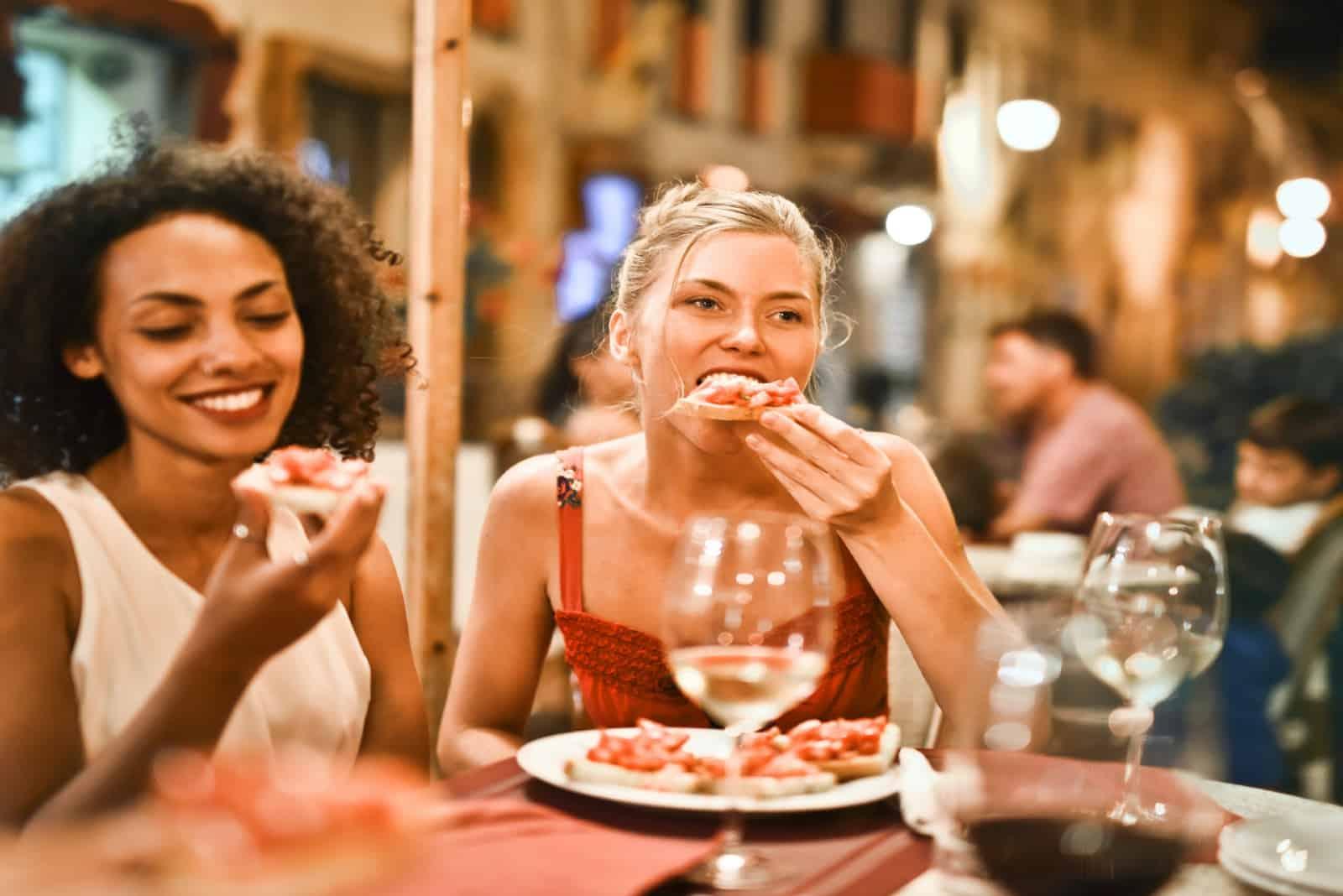 deux femmes en train de manger dans un restaurant