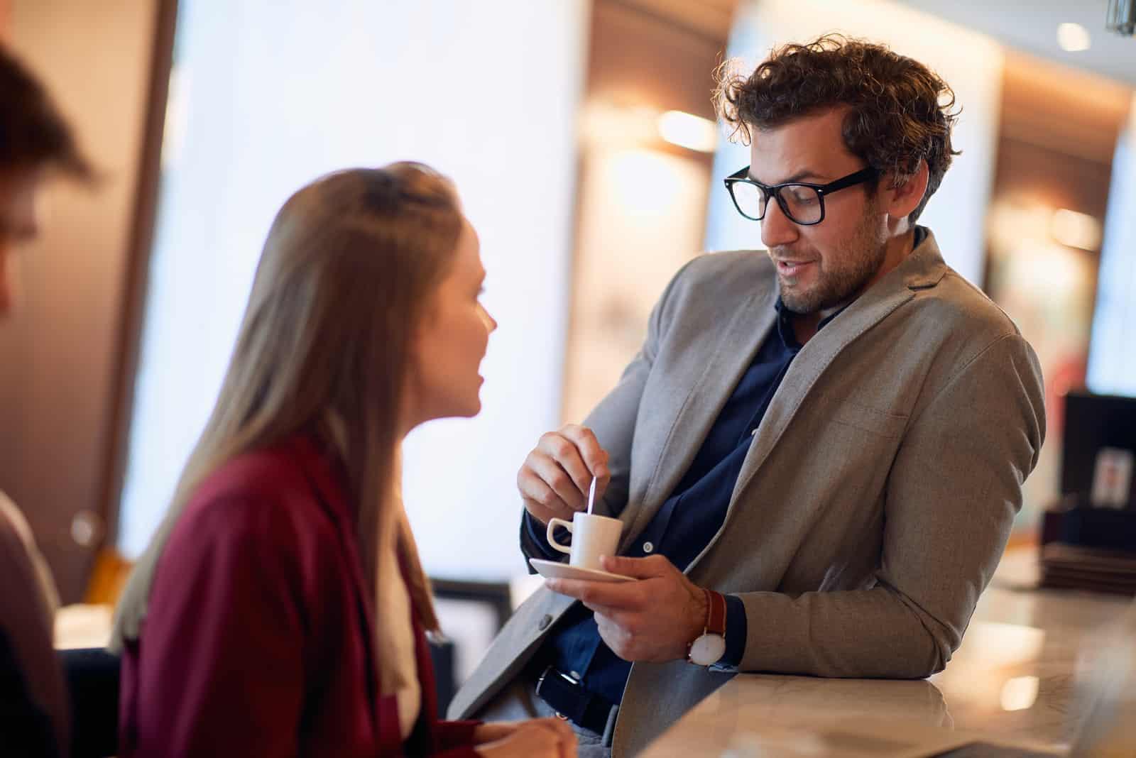 l'homme parle à la femme pendant qu'il s'appuie contre le bar