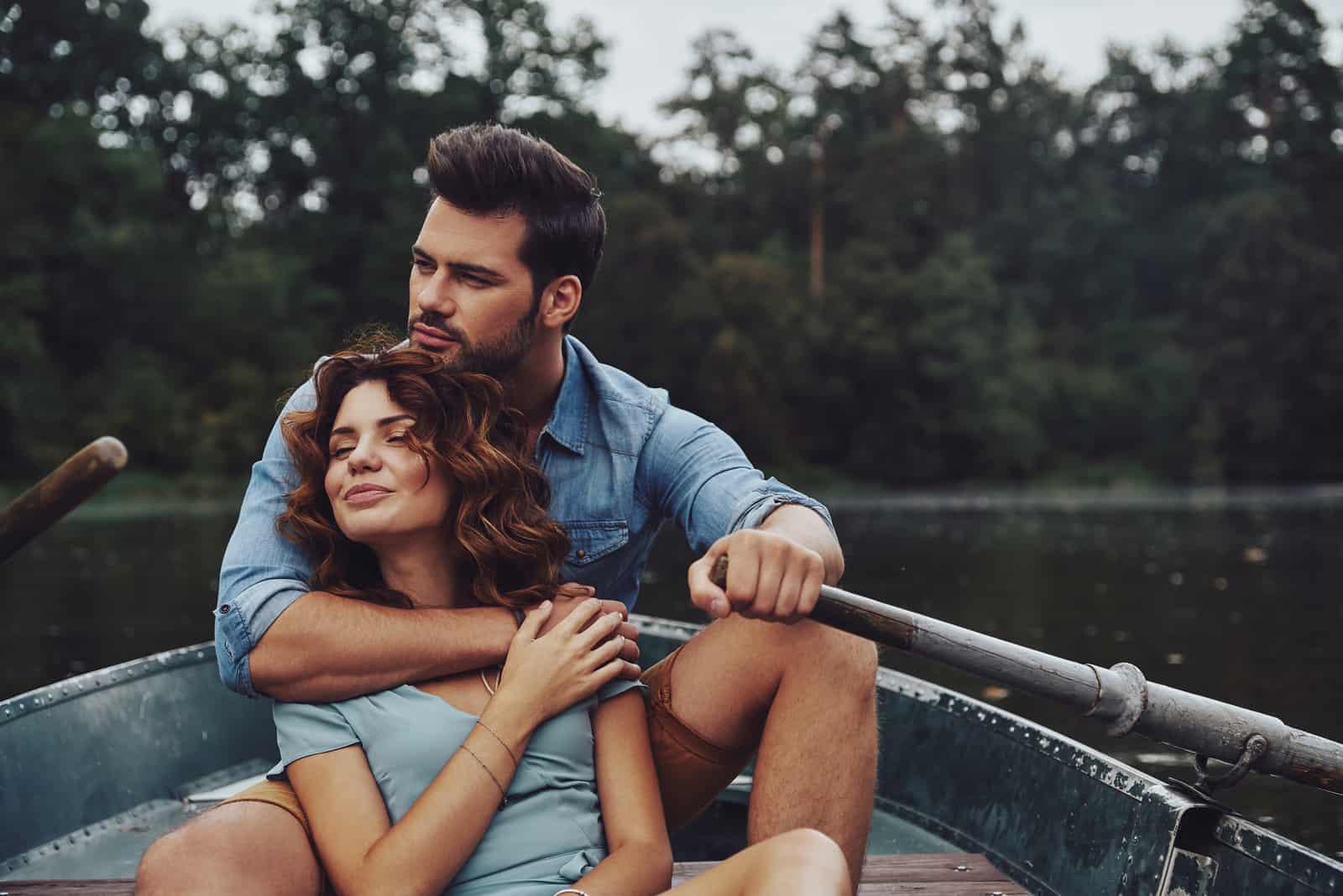 l'homme serra la femme dans ses bras alors qu'ils étaient assis dans le bateau