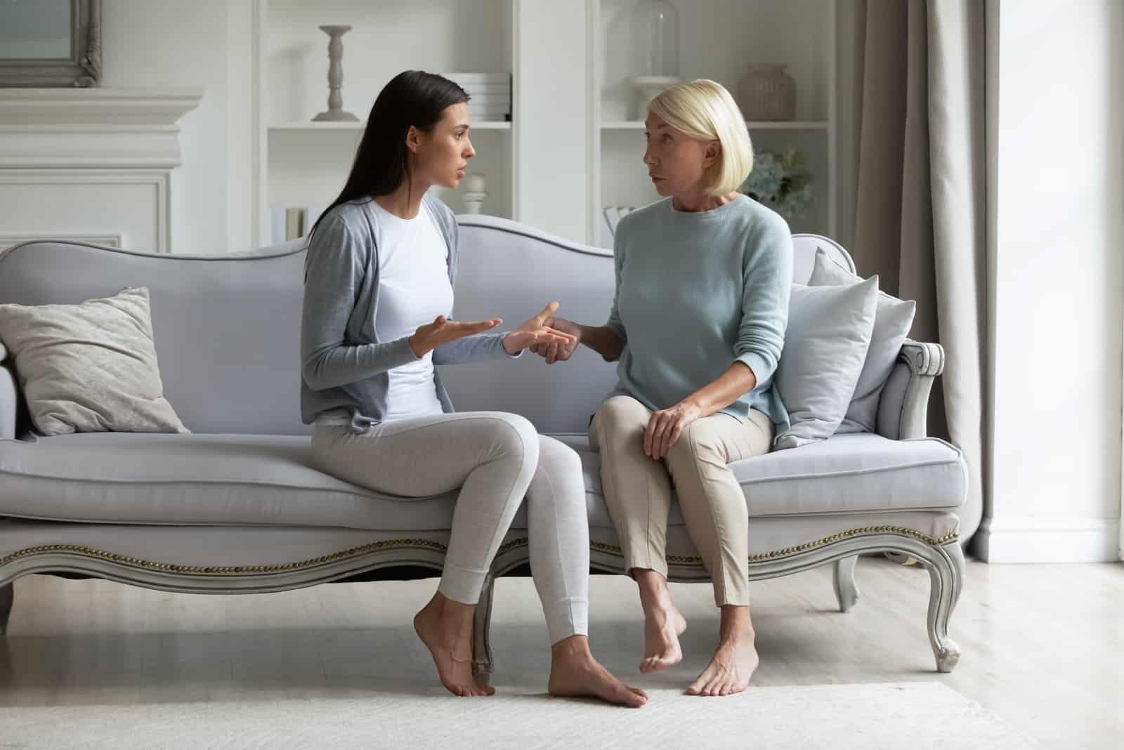 mère et fille discutant assises sur un canapé