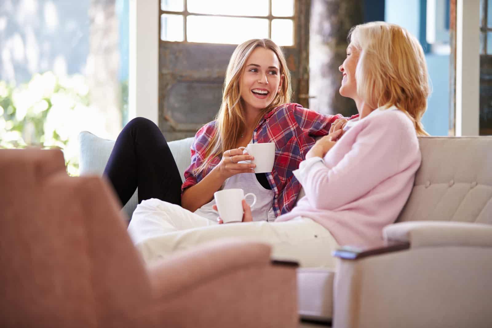 mère et fille prenant un café assises sur un canapé