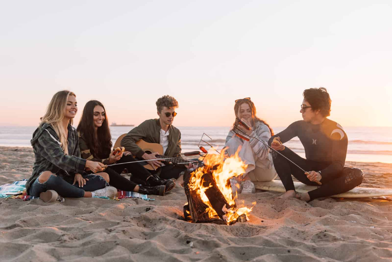 personnes assises sur la plage près d'un feu de camp