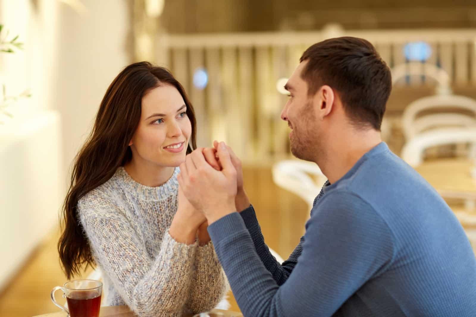 un couple d'amoureux assis se tenant la main pendant qu'ils parlent