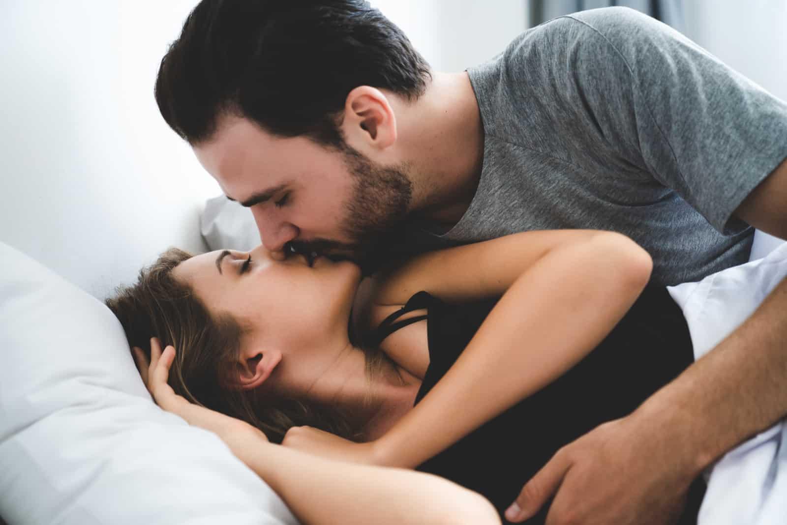 un homme embrasse une femme au lit
