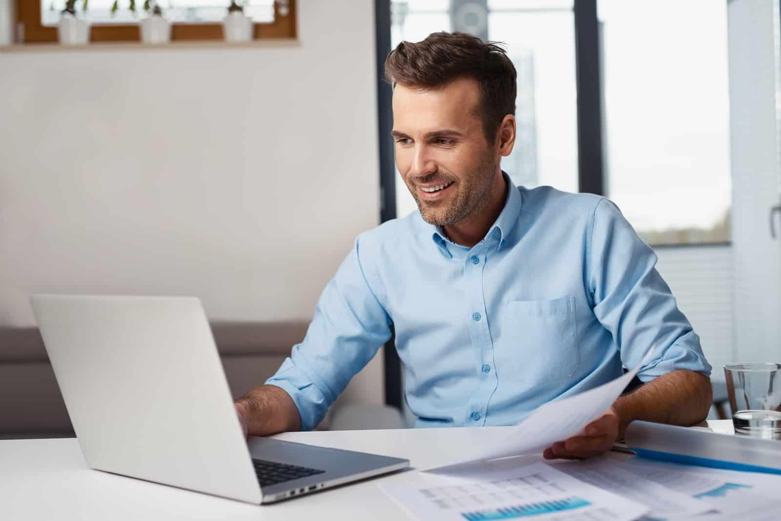 un homme est assis devant un ordinateur portable et travaille