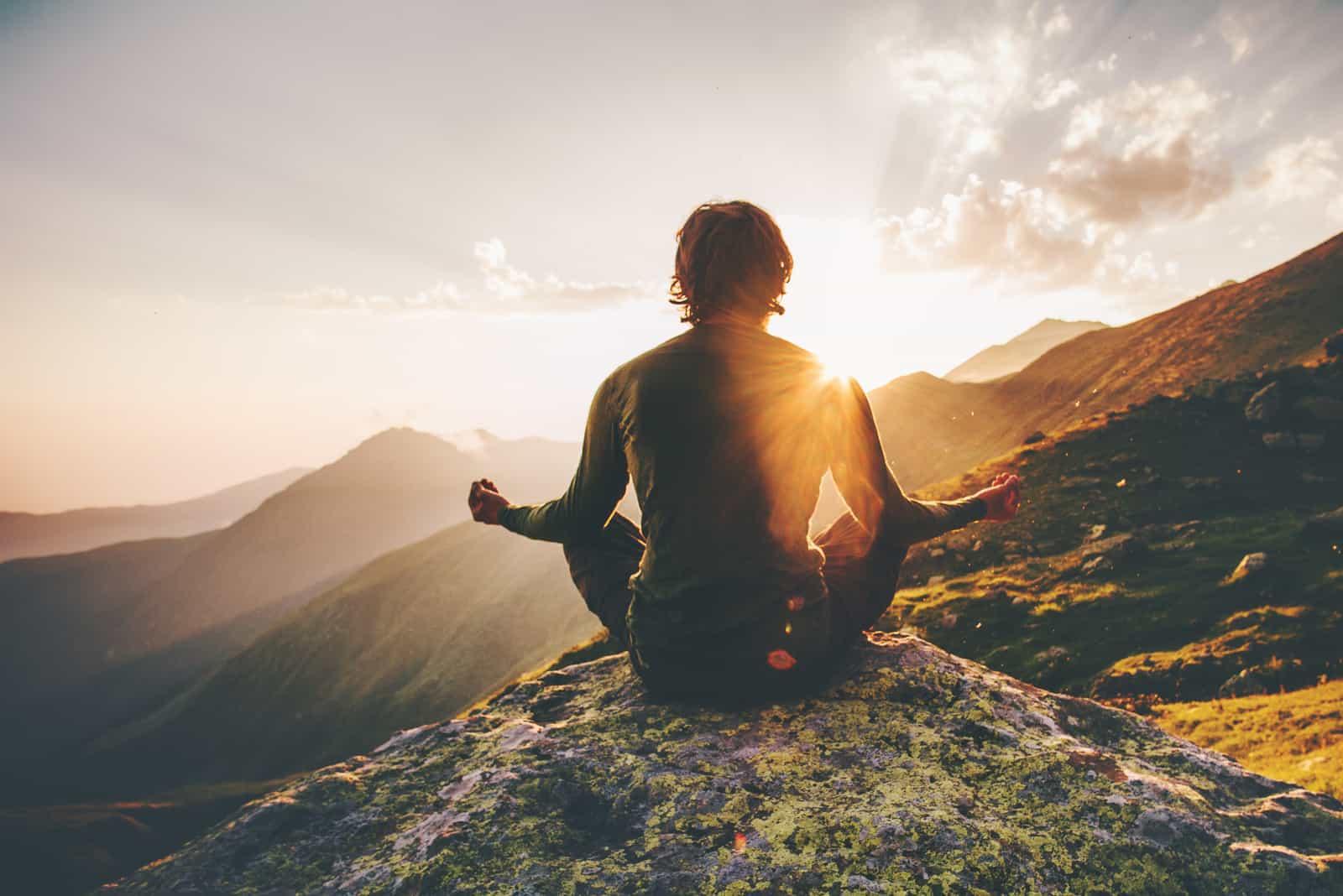un homme est assis sur un mur et médite