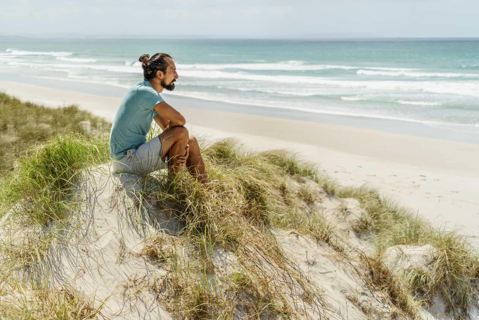 un homme est assis sur une colline et regarde la mer