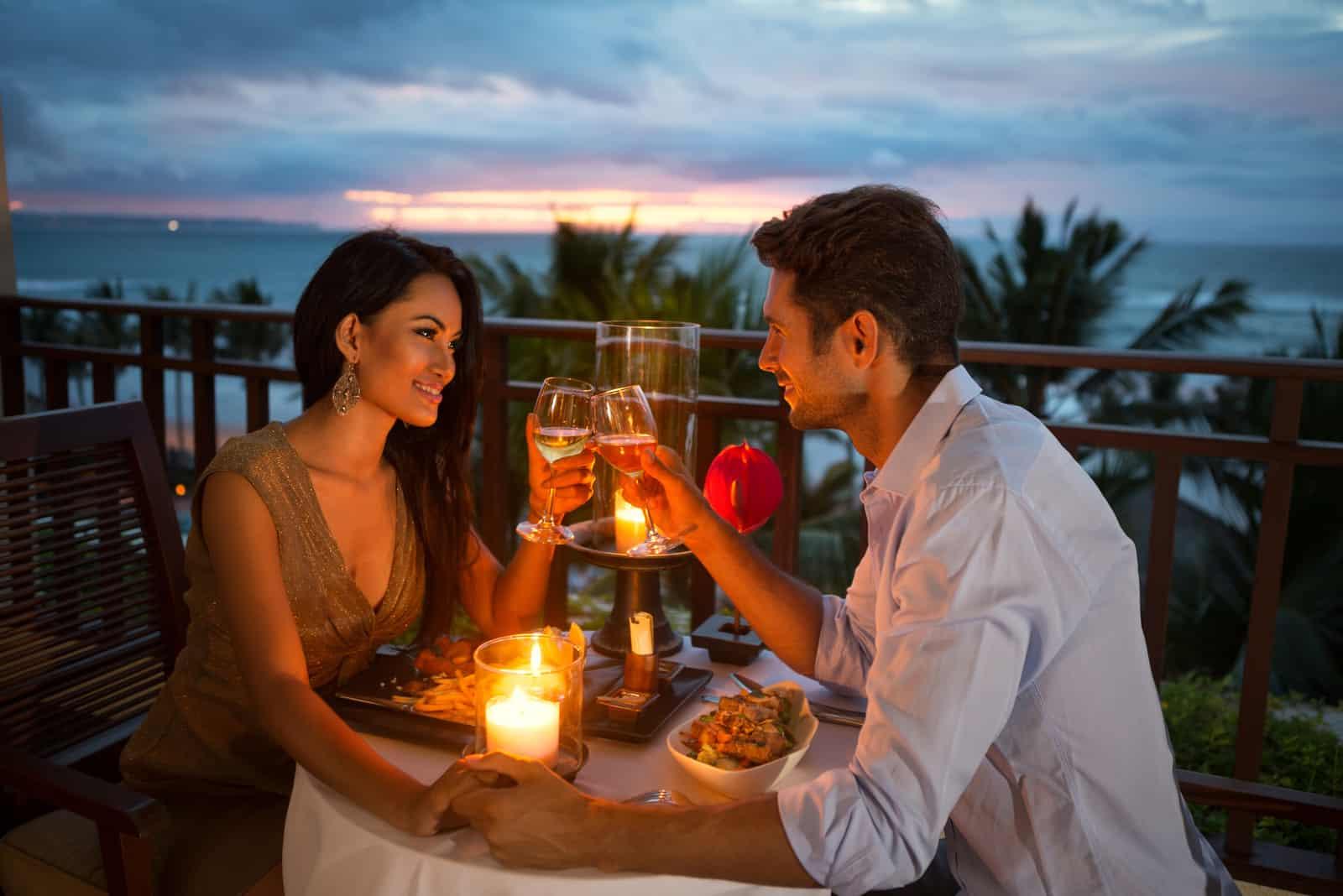 un homme et une femme assis au dîner grillant avec du vin