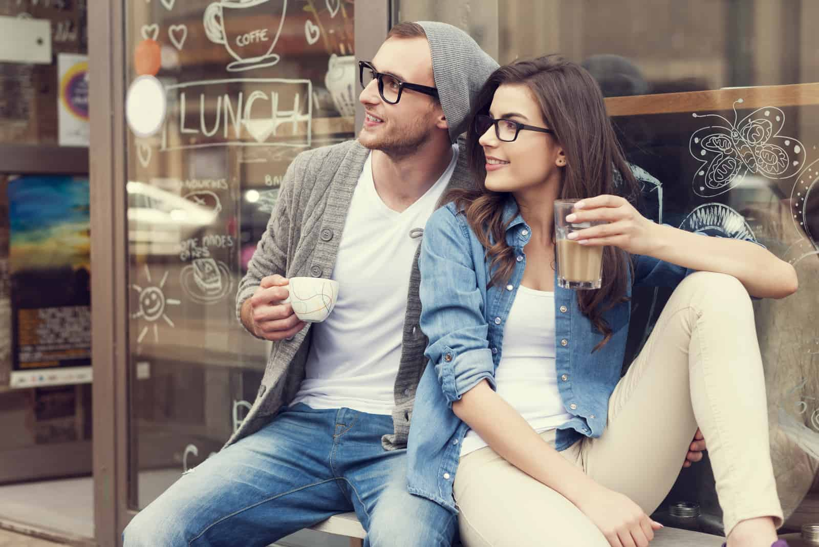 un homme et une femme buvant du café pendant qu'elle détourne le regard