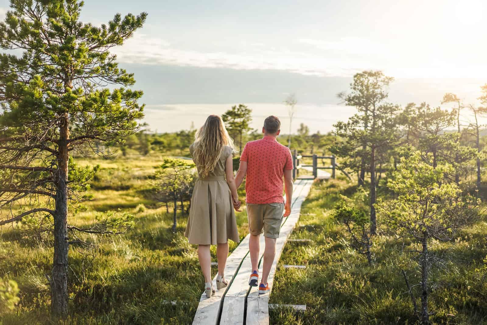 un homme et une femme marchent dans le parc