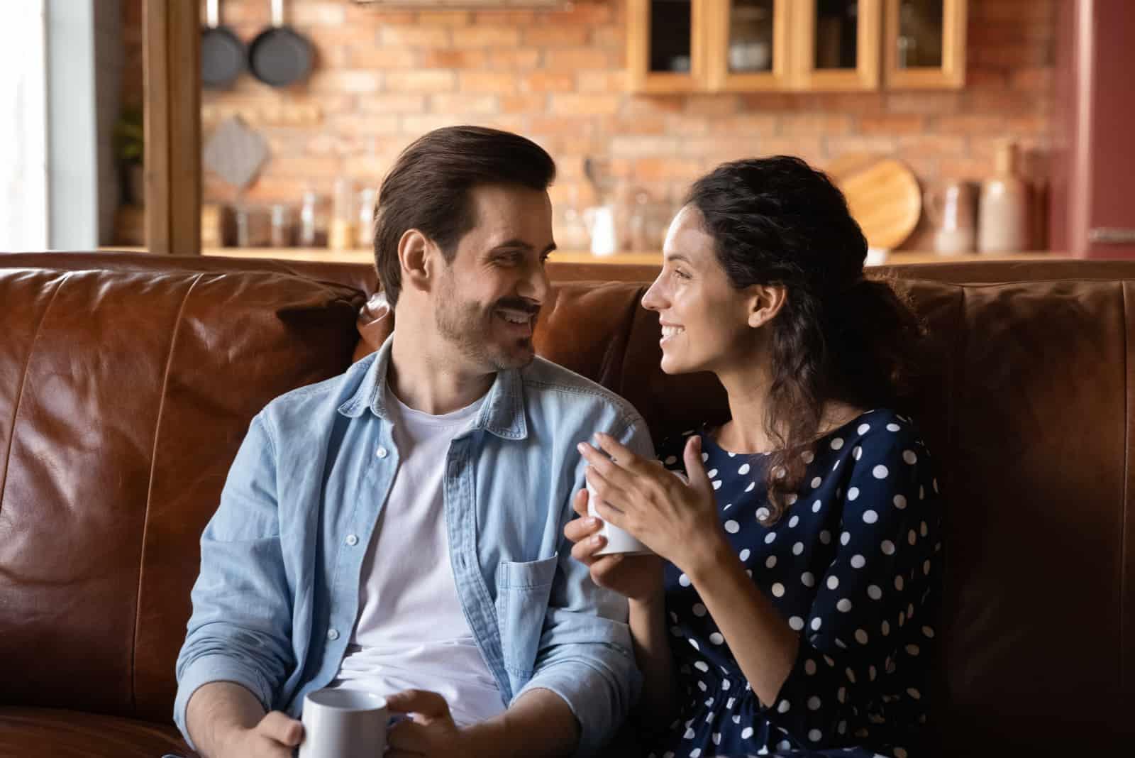 un homme et une femme s'assoient sur le canapé et parlent