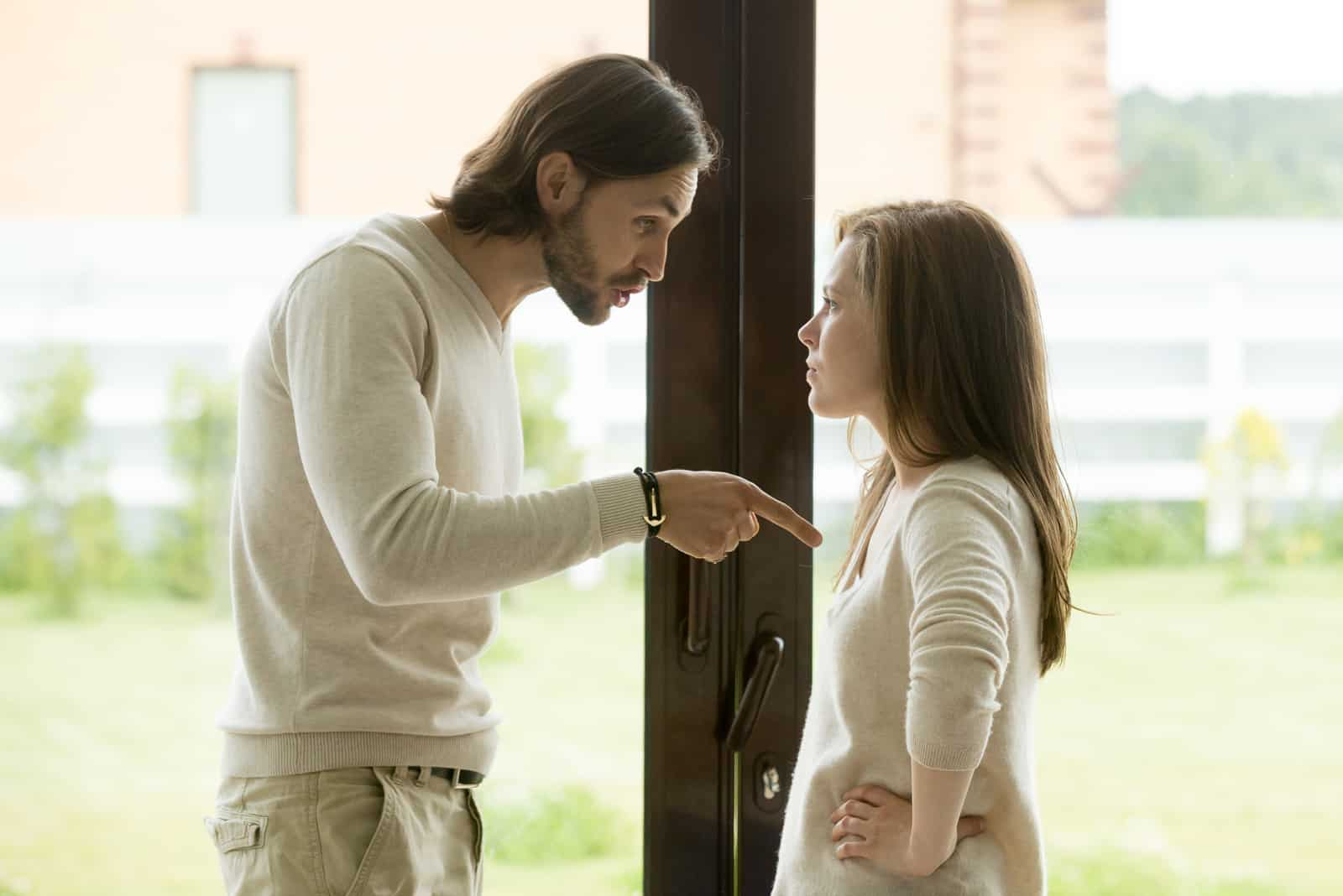 un homme et une femme se tiennent près de la fenêtre alors qu'il lui crie dessus