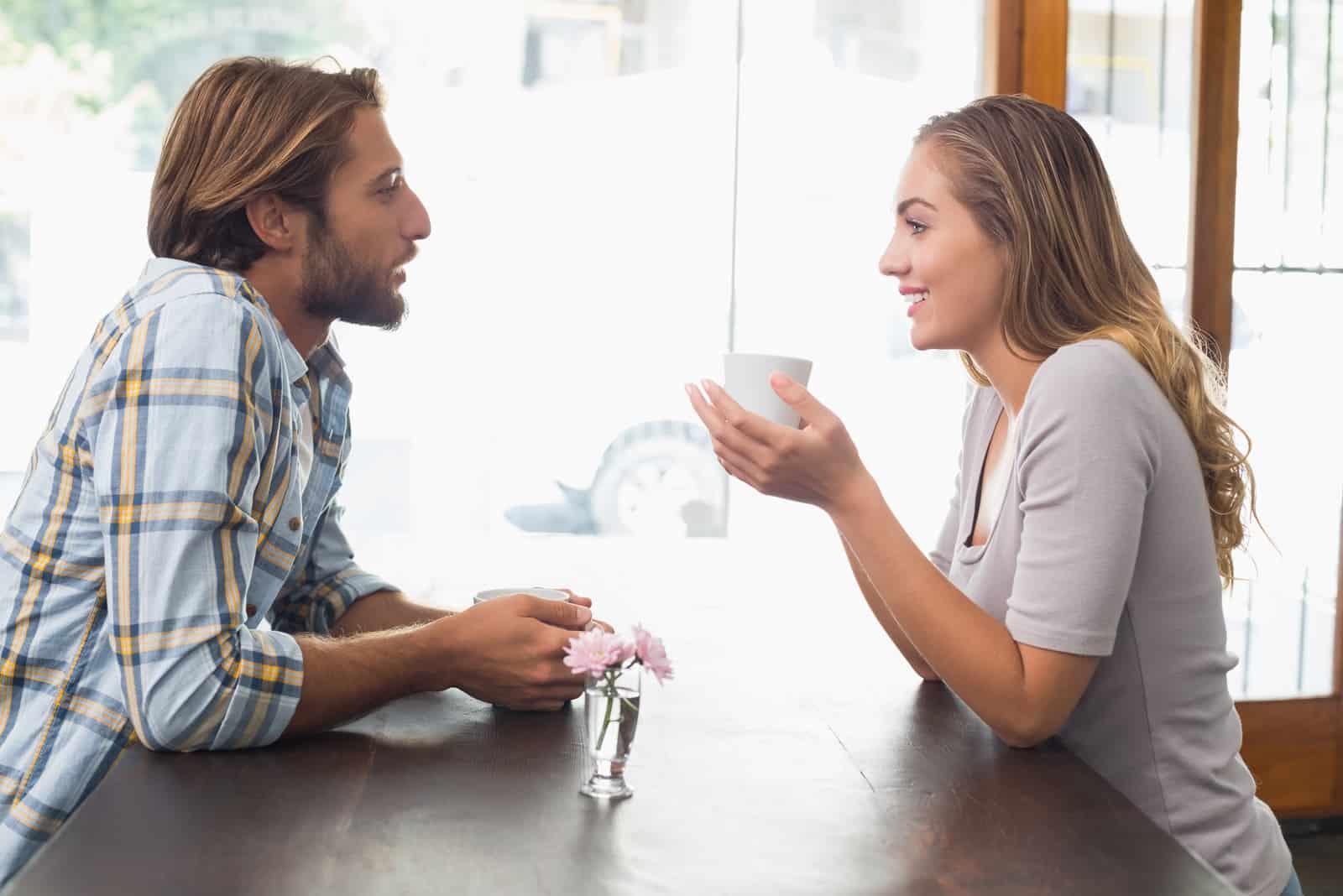 un homme et une femme sont assis à une table autour d'un café et discutent