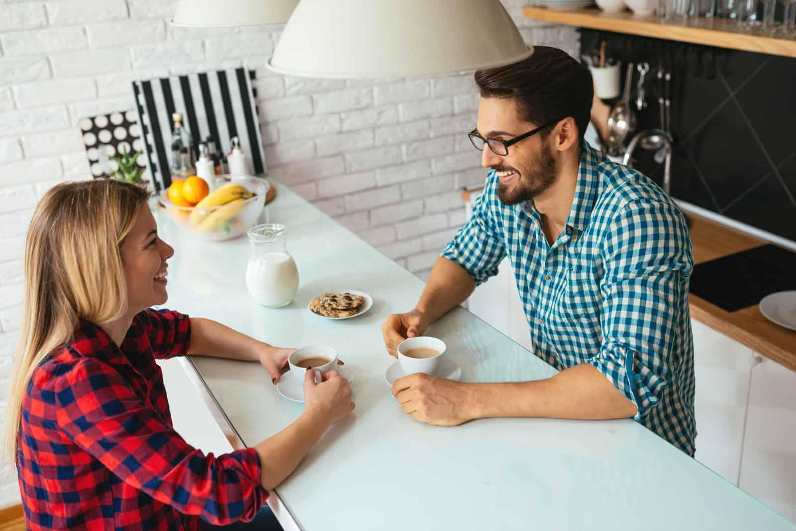 un homme et une femme sont assis dans la cuisine et parlent