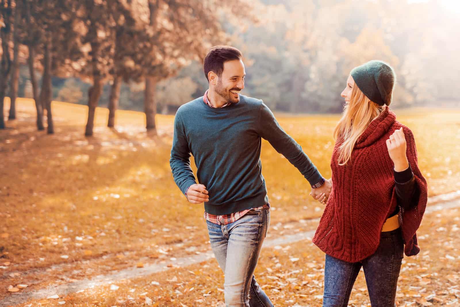 un homme et une femme souriants courent à travers le champ