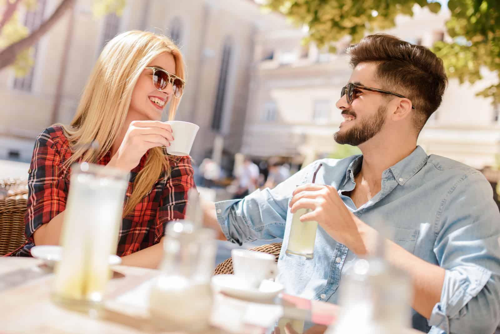 un homme et une femme souriants s'assoient à l'extérieur et parlent autour d'un café