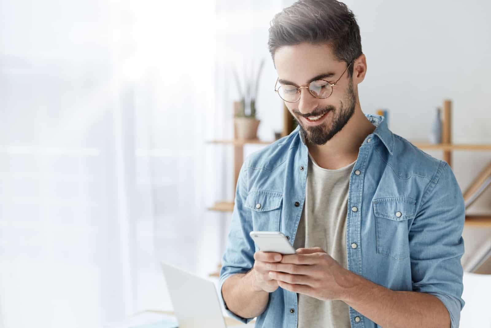 un homme souriant avec des lunettes et un bouton sur le téléphone
