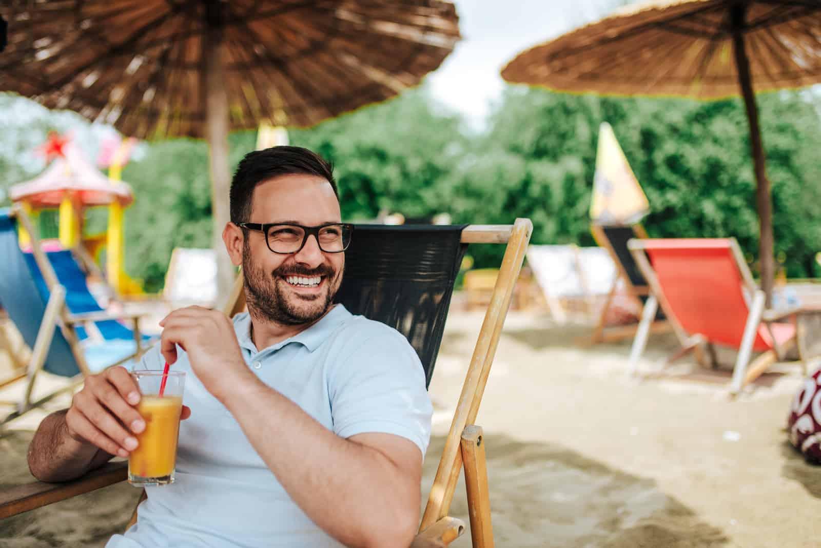 un homme souriant est assis sur la plage et boit un verre